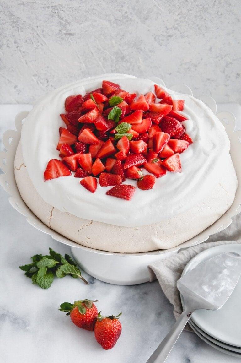 three quarters view of strawberry pavlova on a white cake stand