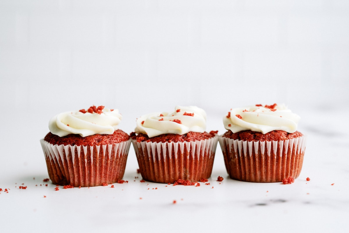 a line of red velvet cupcakes with cream cheese frosting