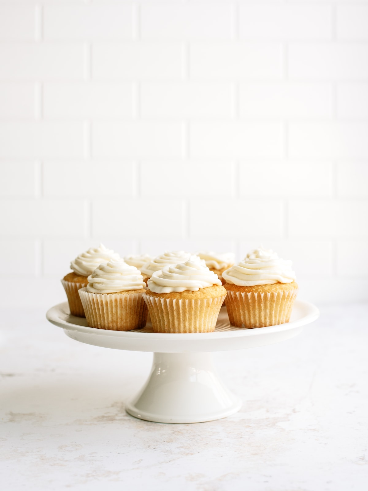 frosted vanilla cupcakes on a white cake platter