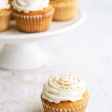 frosted vanilla cupcakes on a white cake platter with one cupcake on the counter in front of it