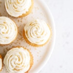 top down view of frosted vanilla cupcakes on a white cake platter