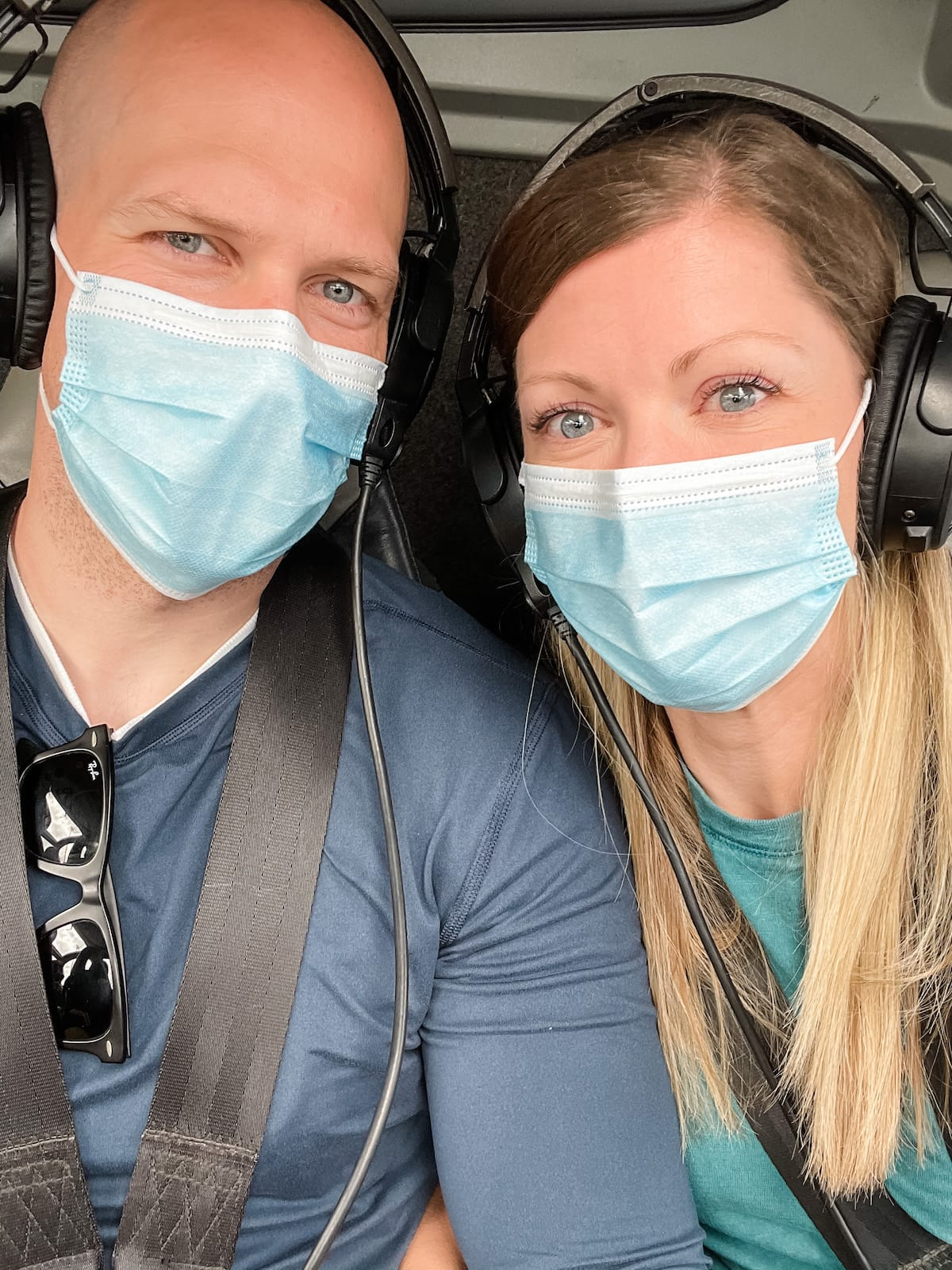 man and woman with masks on in helicopter