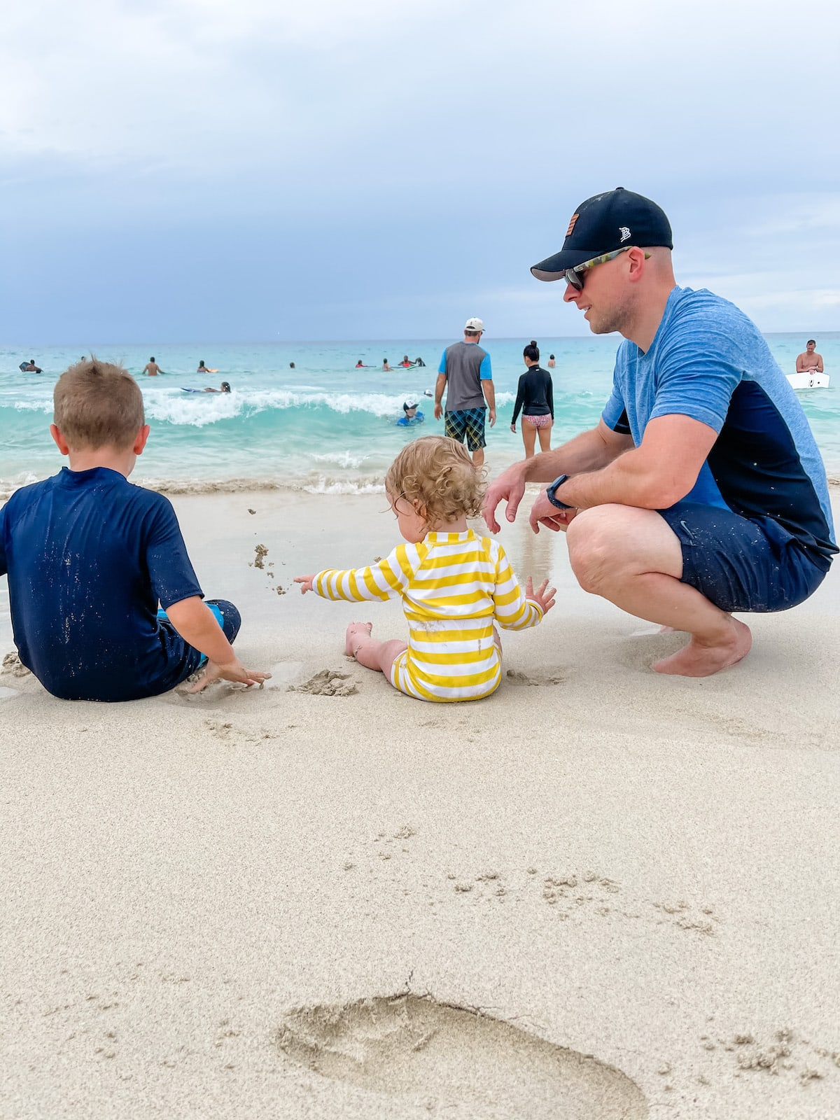 dad with two boys sitting on beach