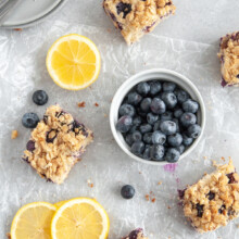 slices of lemon blueberry cake among a bowl of blueberries and lemon slices