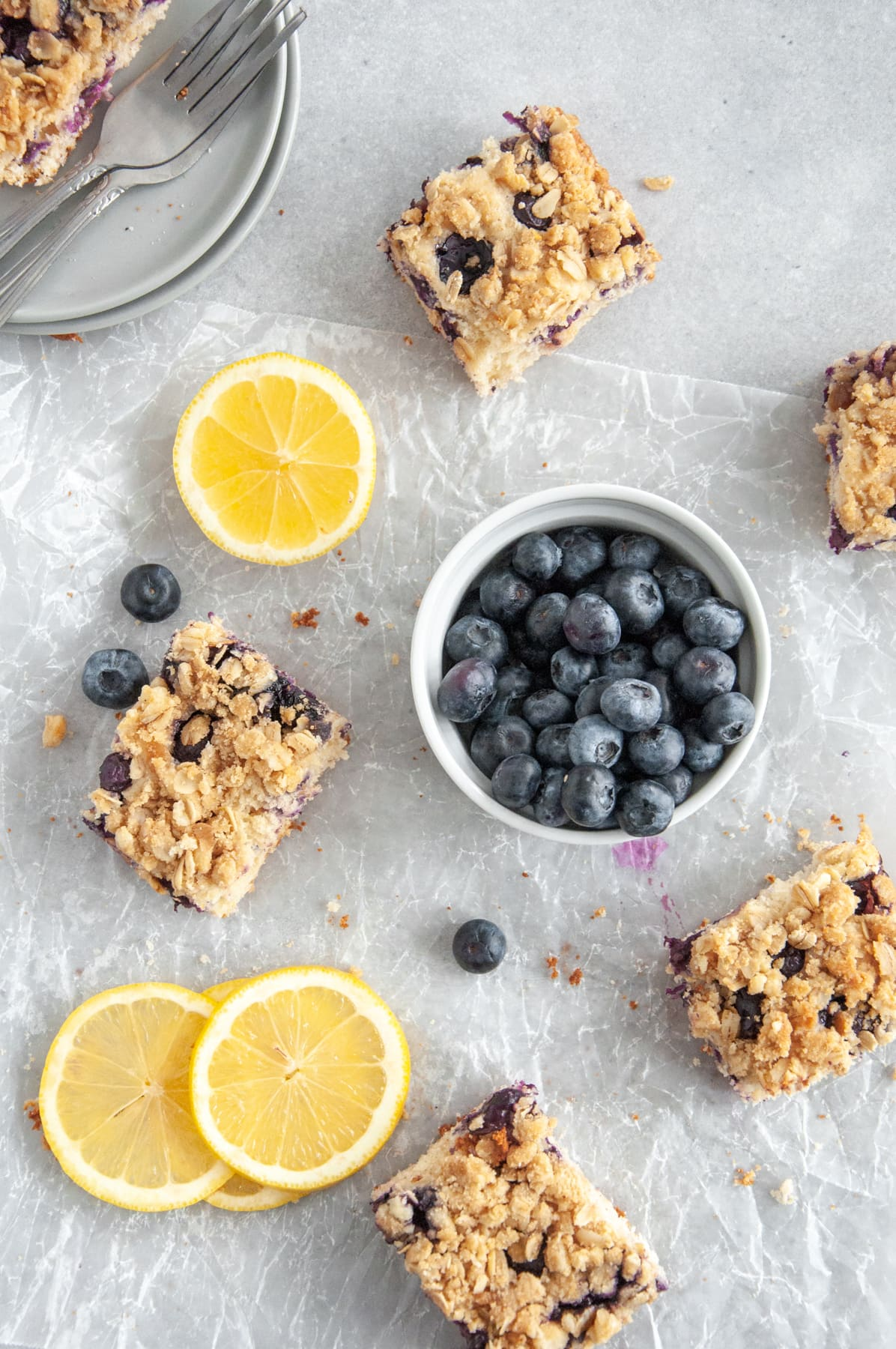 slices of lemon blueberry coffee cake among a bowl of blueberries and lemon slices