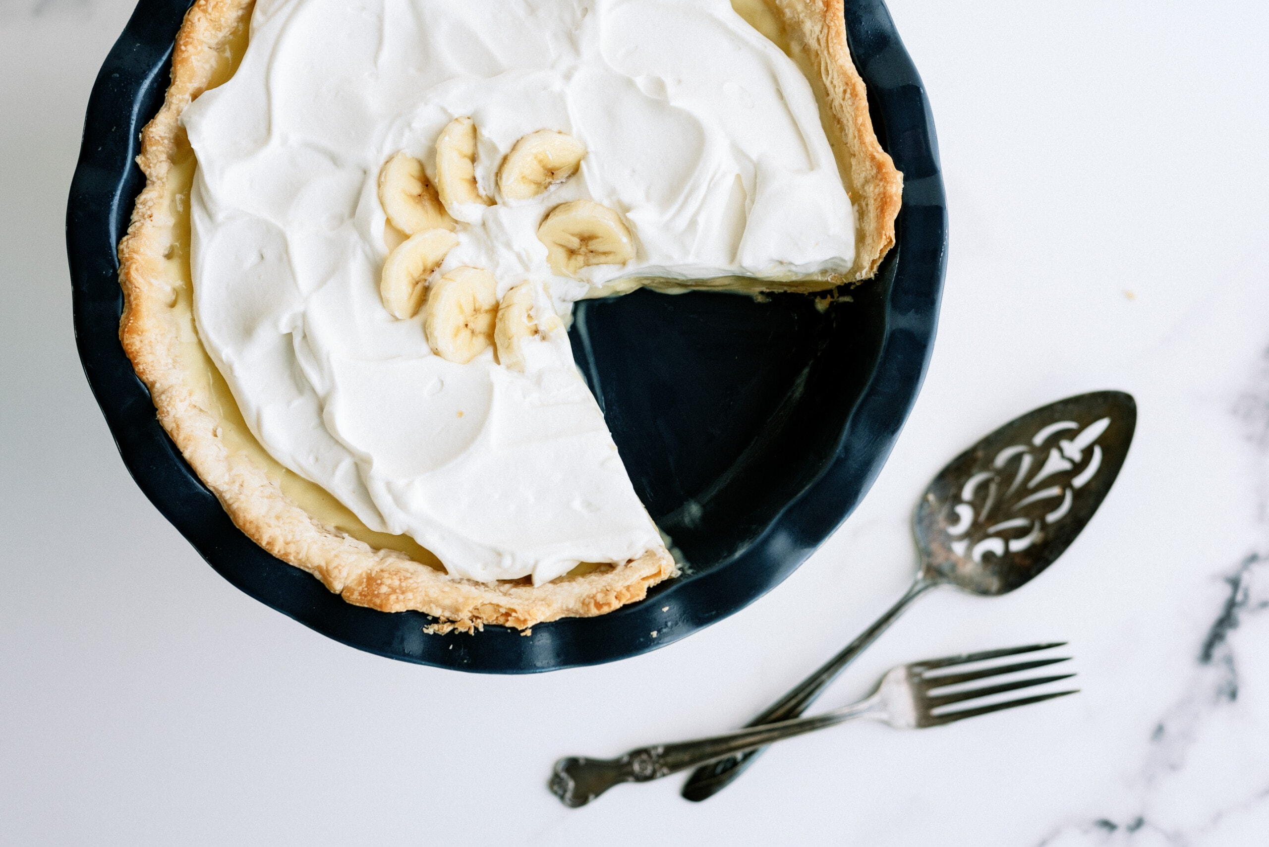 banana cream pie with a slice taken out of it