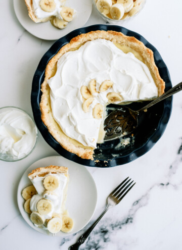 banana cream pie with a slice taken out of it. the slice is on a white plate next to the whole pie