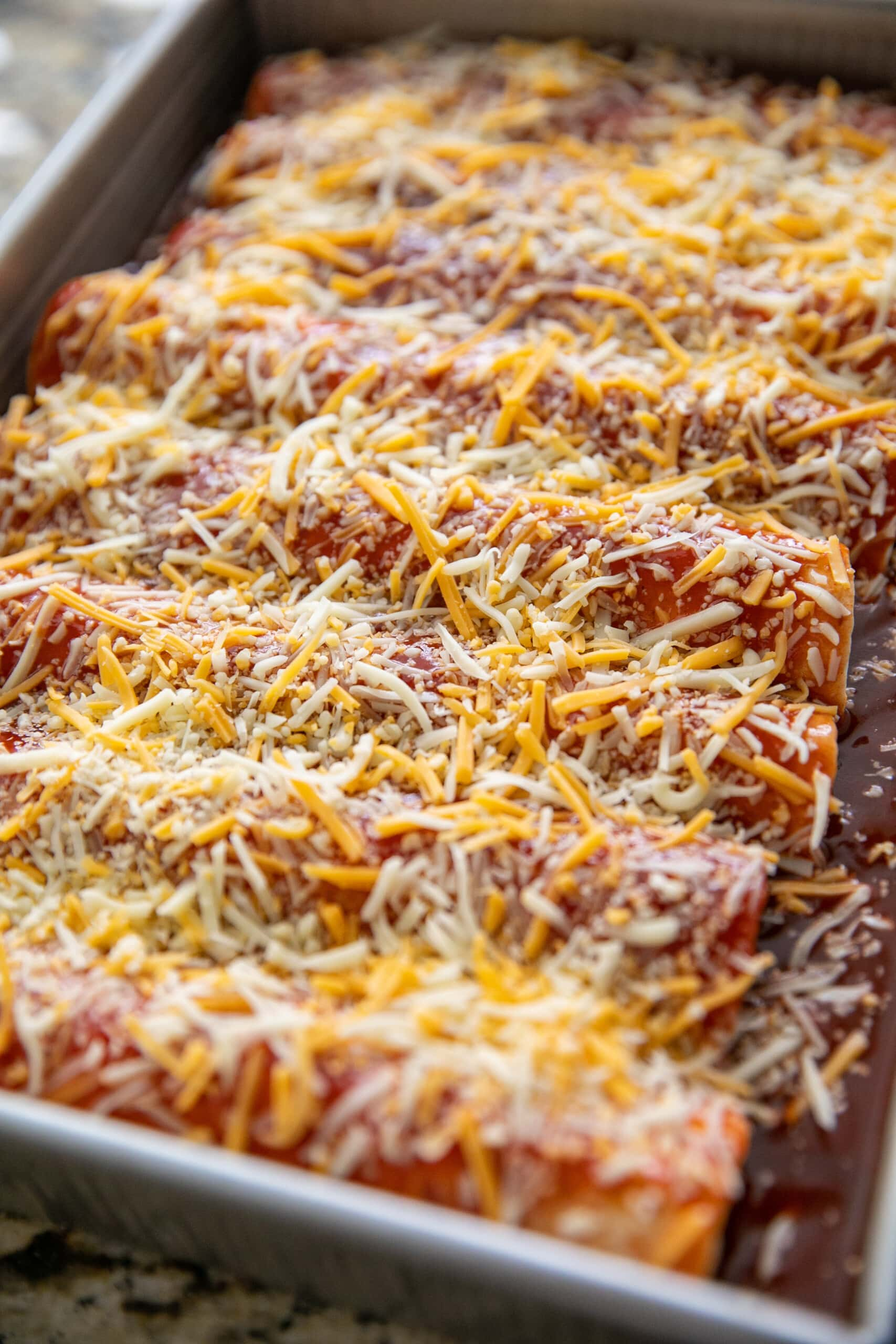 unbaked beef enchiladas in a baking dish with unmelted cheese on top