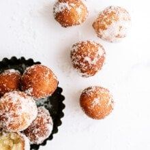 top down view of donut holes in a bowl and on the counter