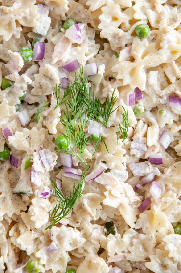 close up of adding dill and red onions to tuna pasta salad