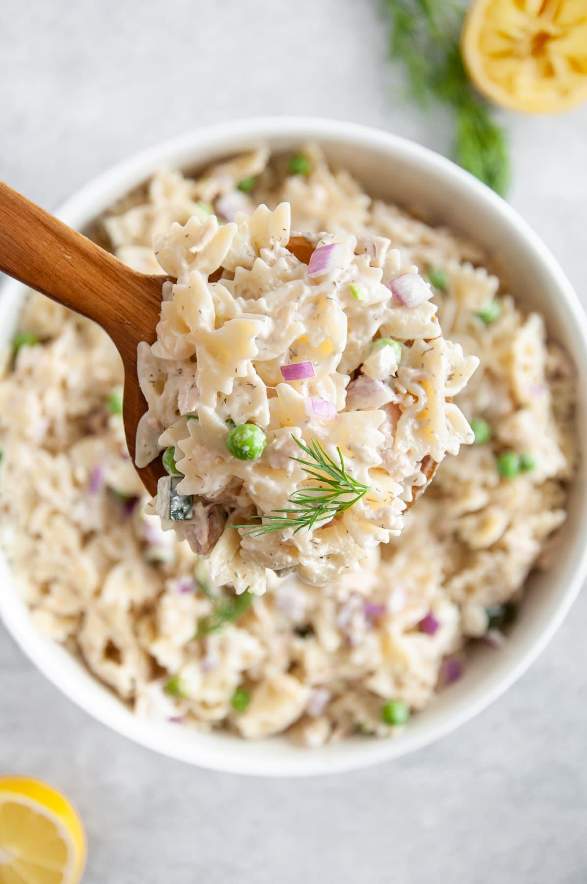scooping tuna pasta salad out of pit with a wooden spoon
