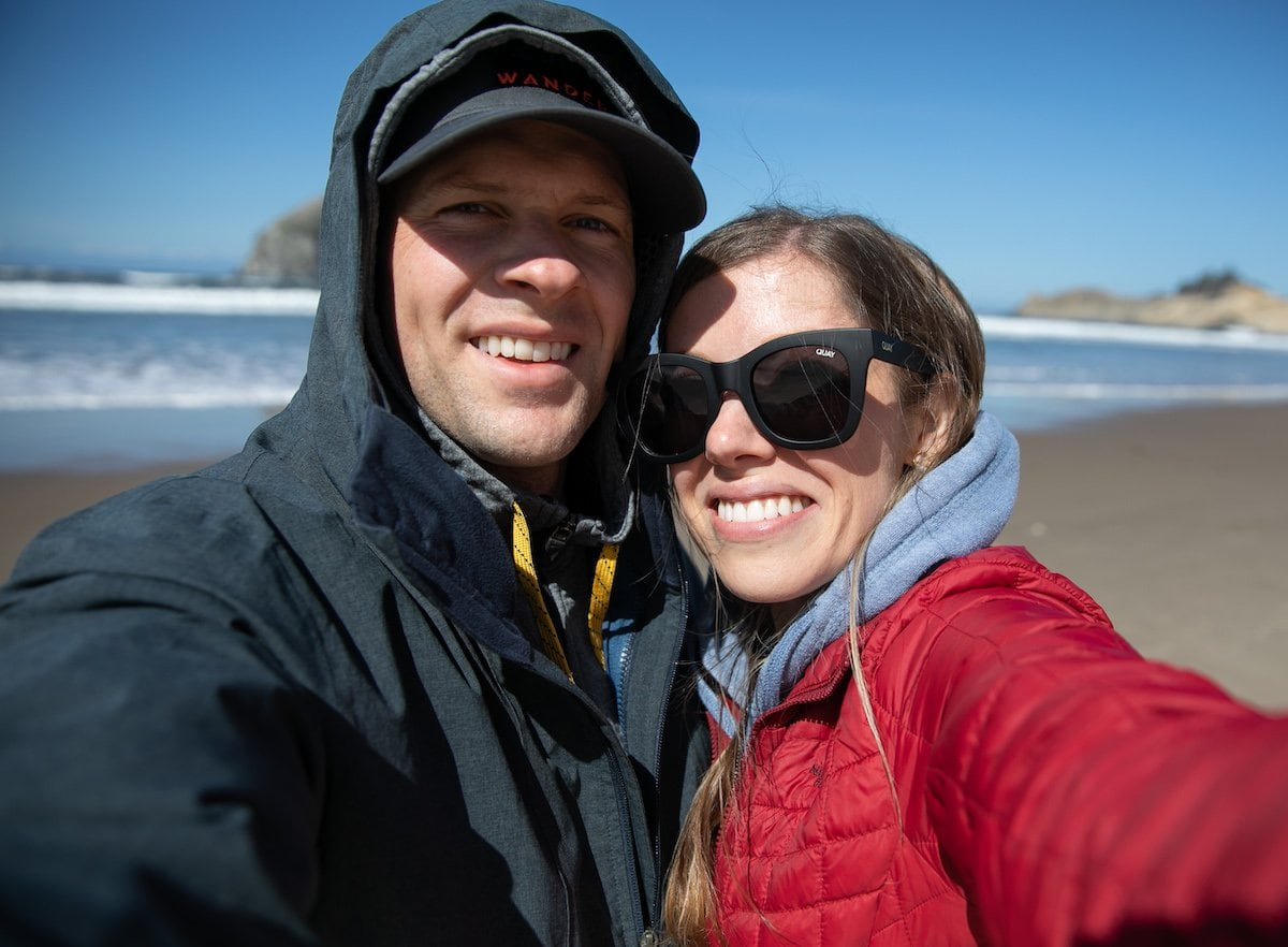 man and woman taking selfie on beach