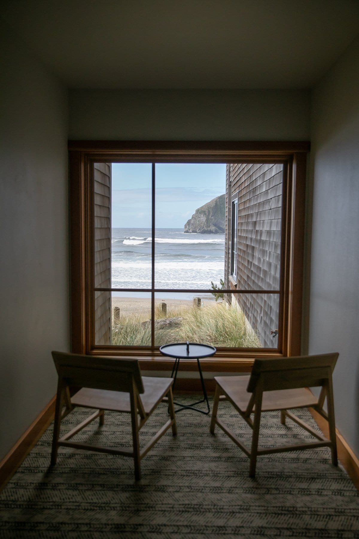 two chairs facing a window of beach
