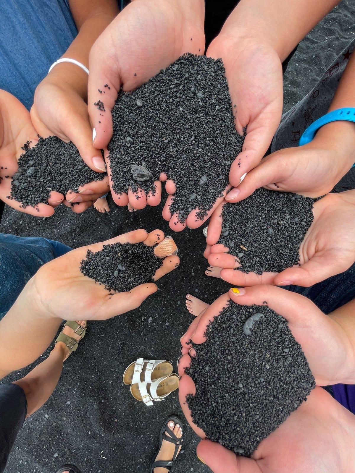 hands holding black sand