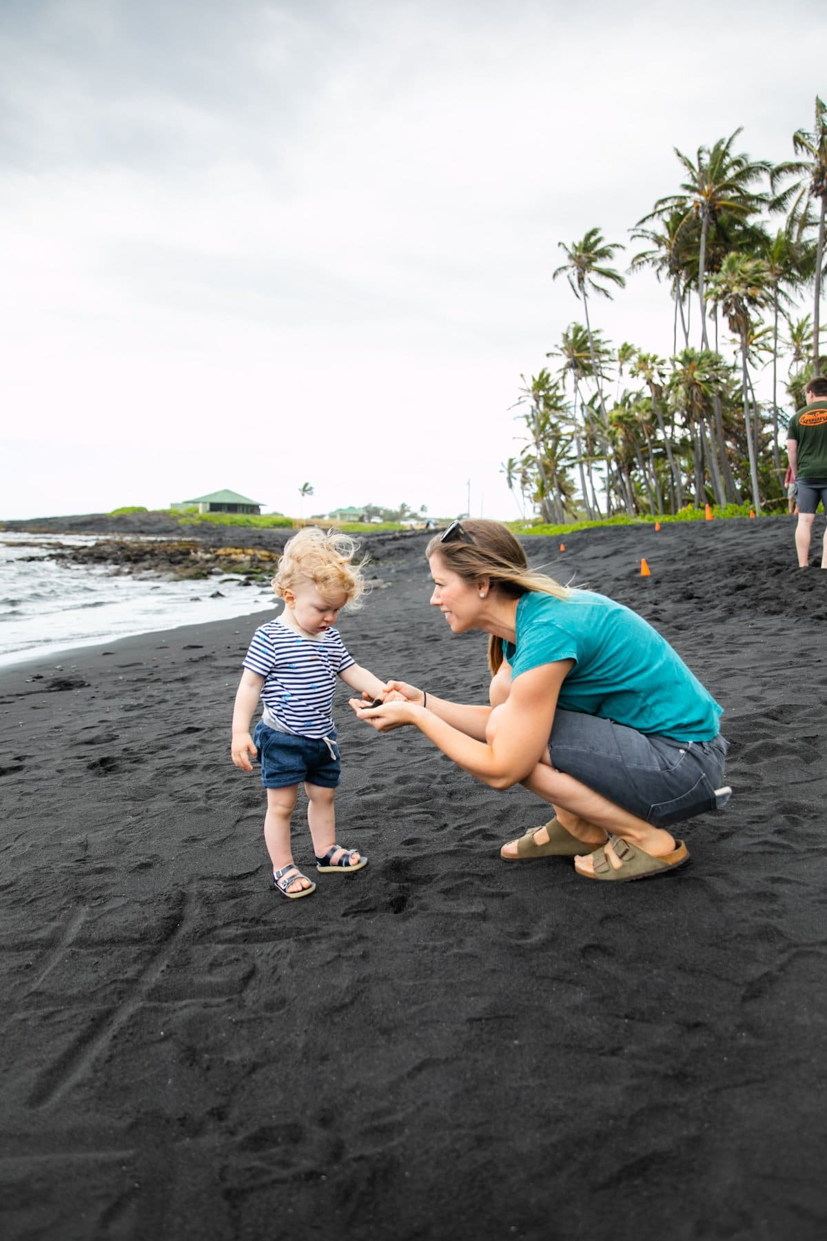 mom with toddler on black sand beach