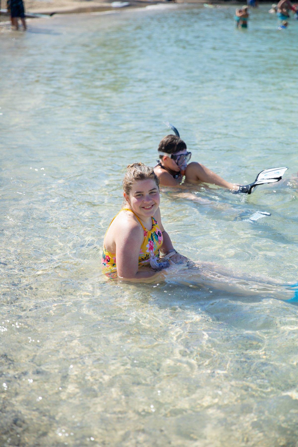 girl smiling while sitting in ocean