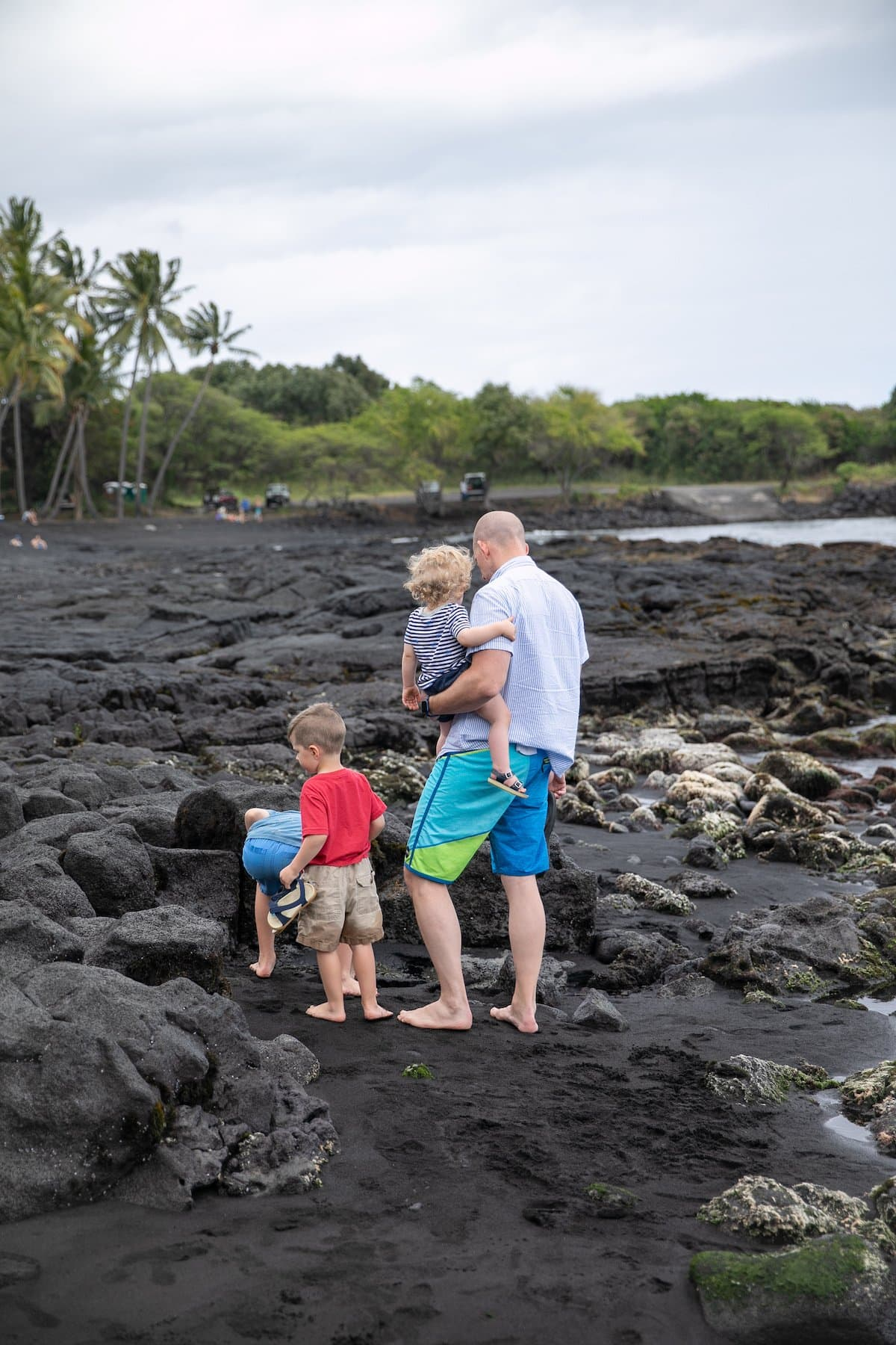 dad with three boys looking at tide pools