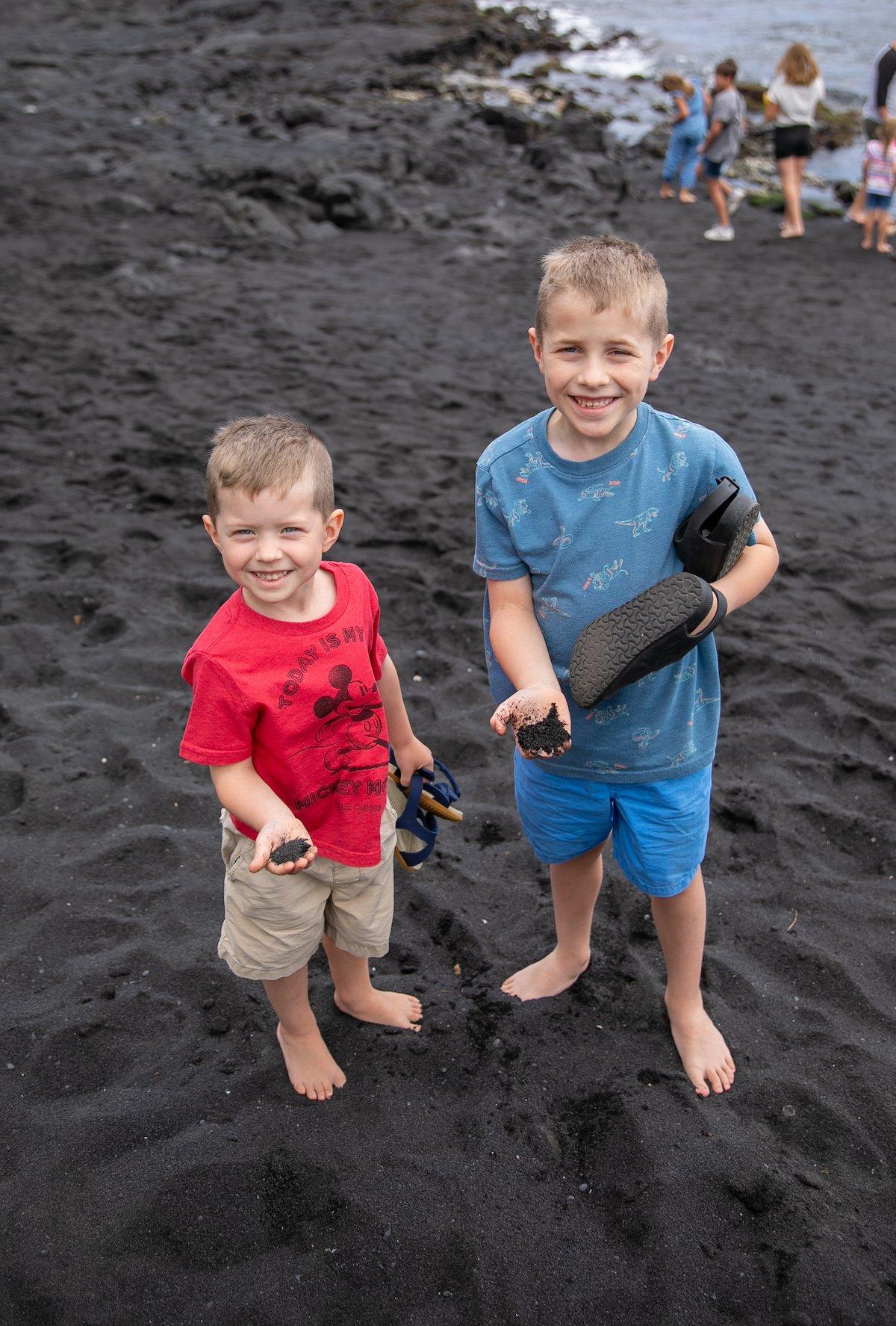 two boys holding black sand