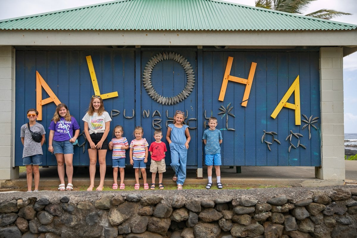 kids posing in front of aloha sign