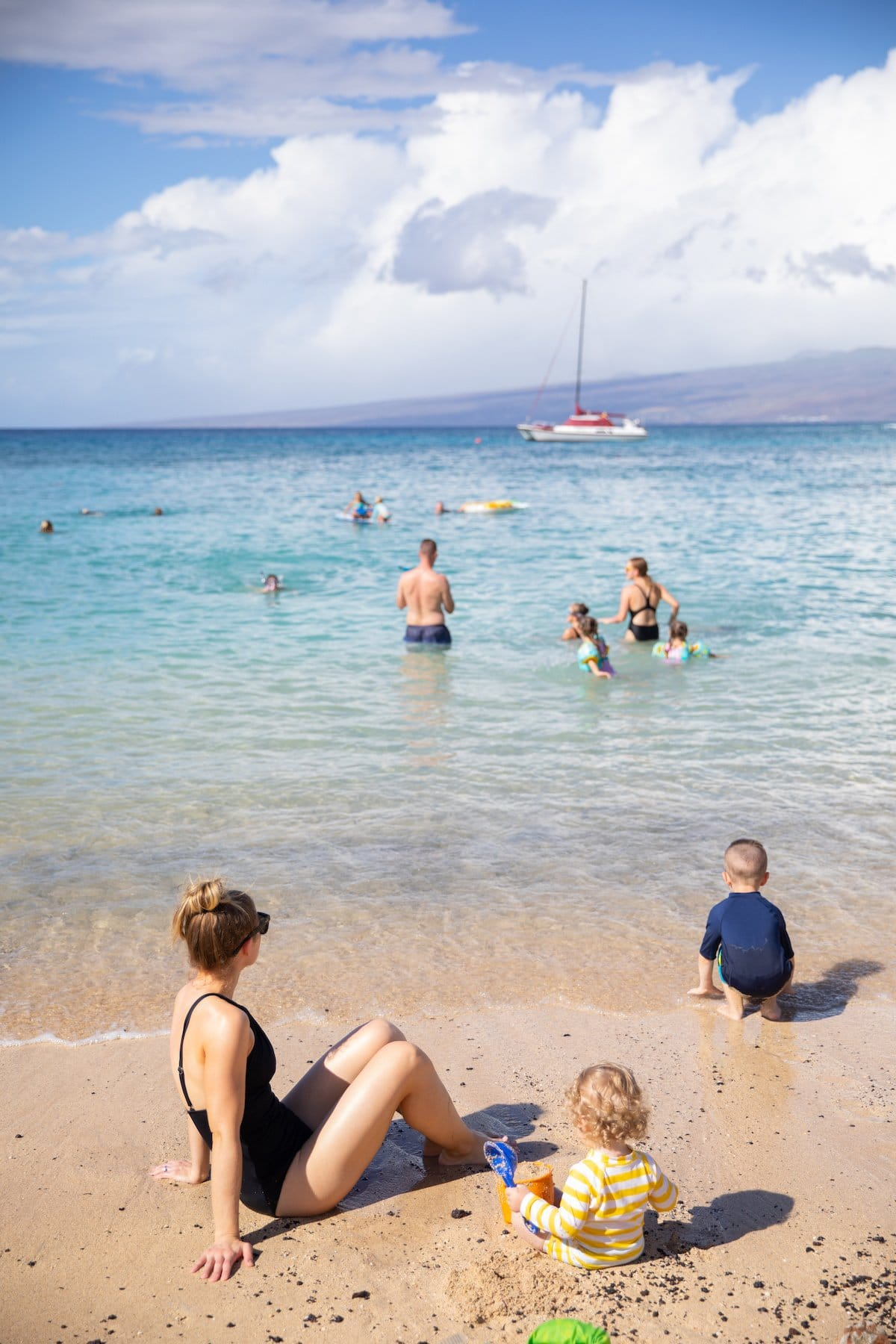 parent and kids playing in shallow ocean water and sand