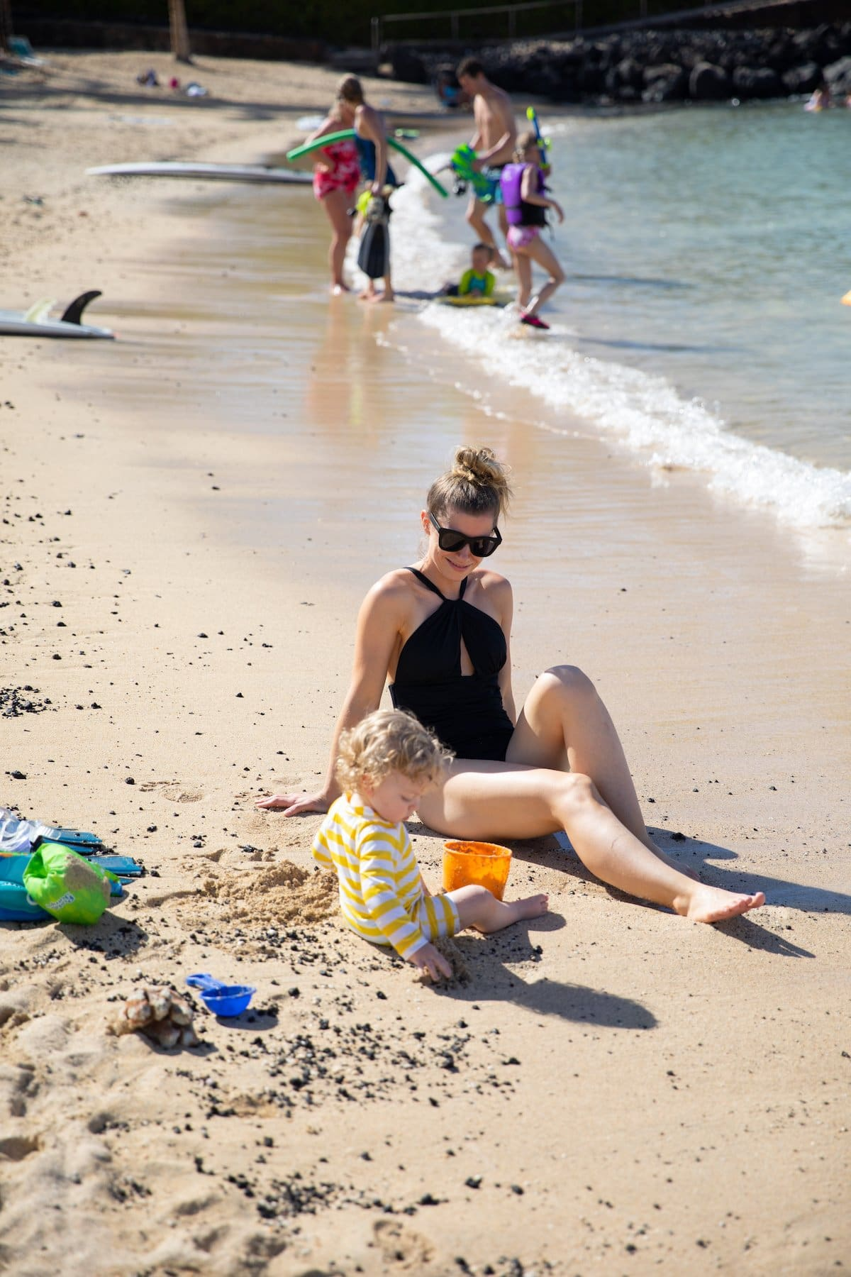 mom and baby playing in sand
