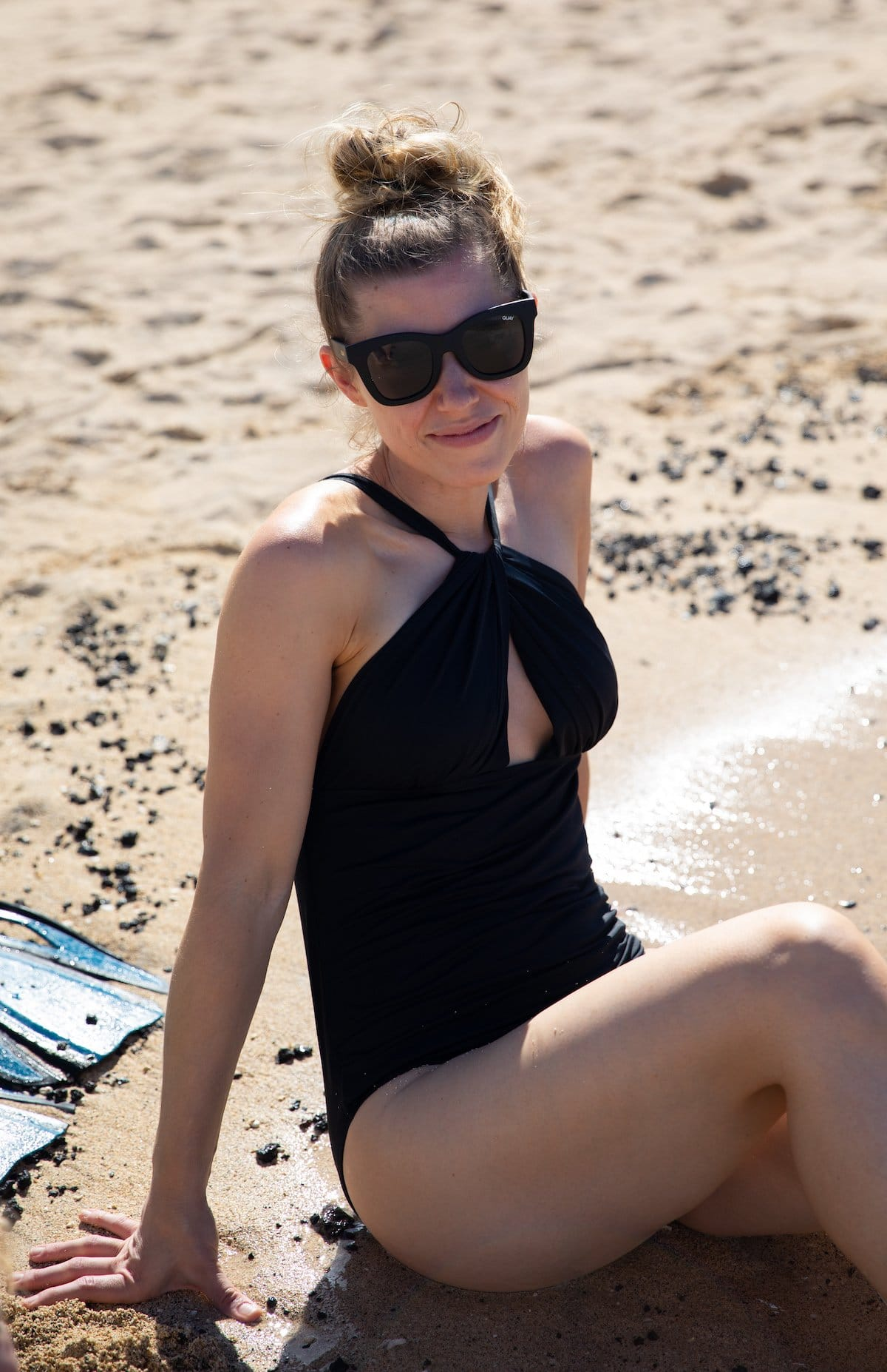lady sitting on sand in swimsuit