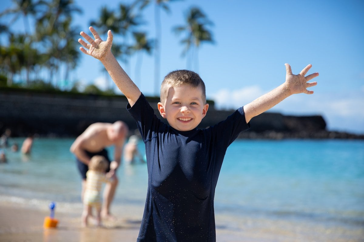 boy with arms up smiling