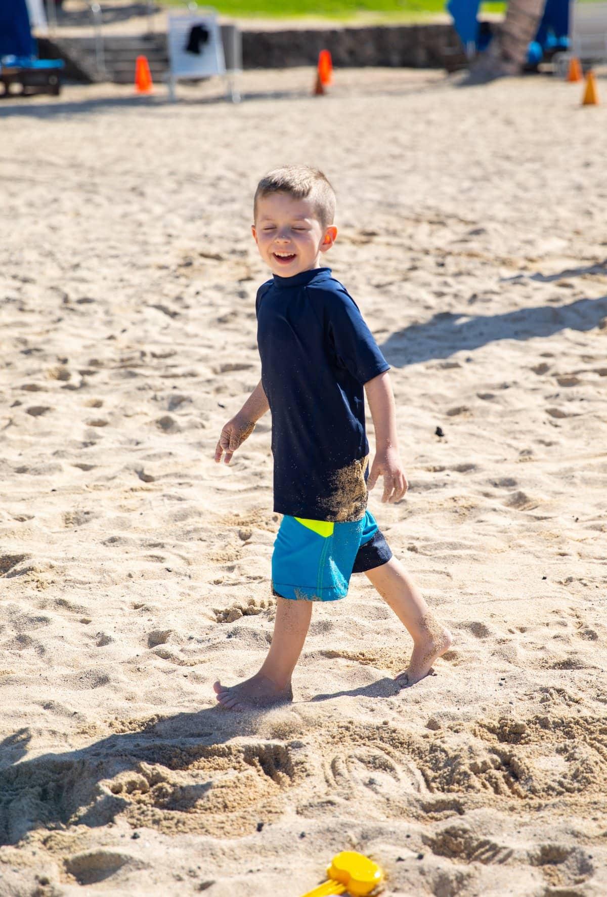 boy walking on sand