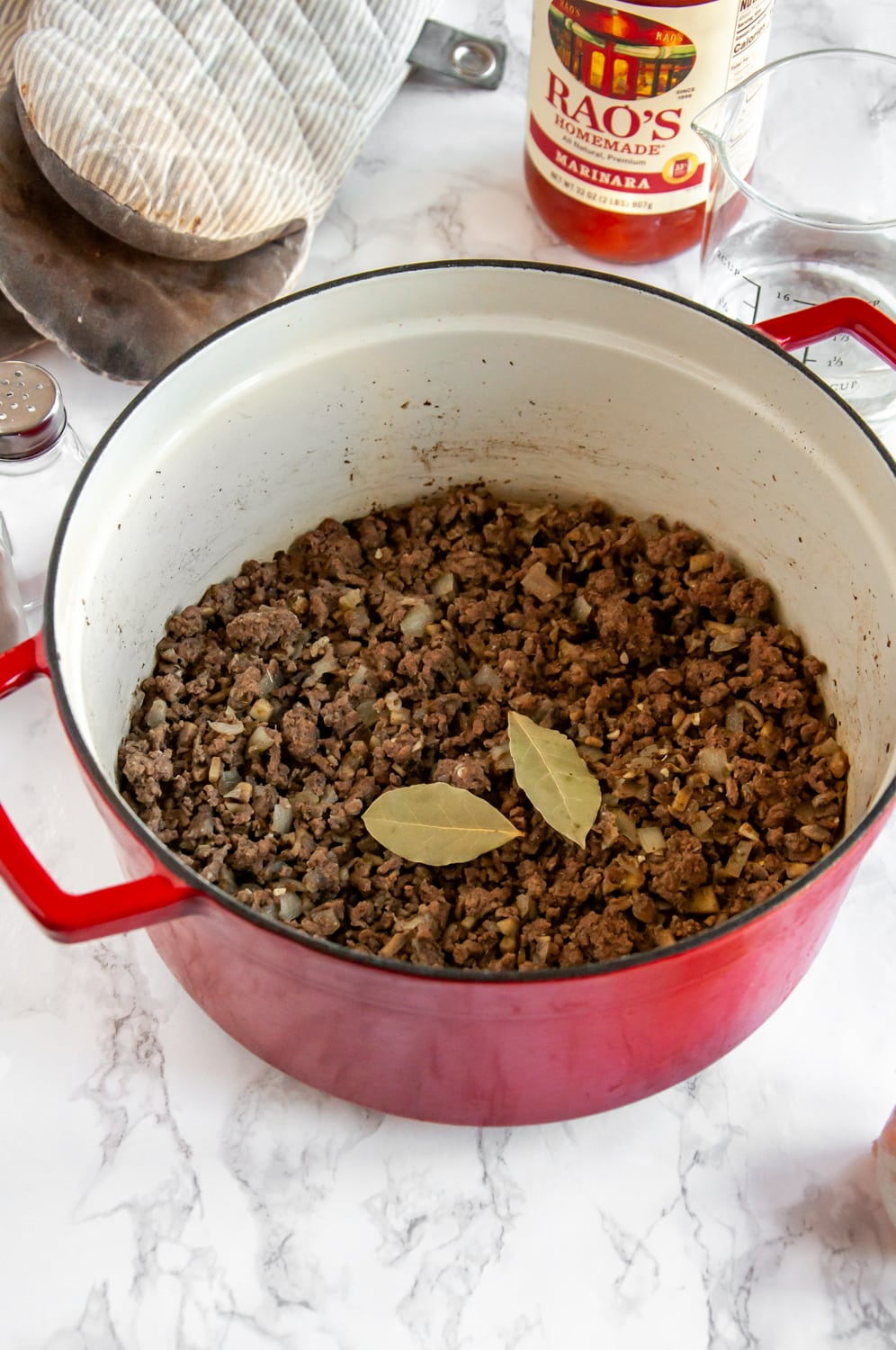 ground beef and other ingredients in a red cooking pot