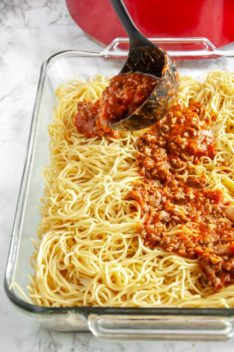 spreading red sauce over cooked spaghetti in a glass baking dish