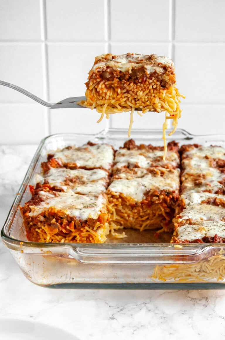 scooping a slice of baked spaghetti out of a glass baking dish