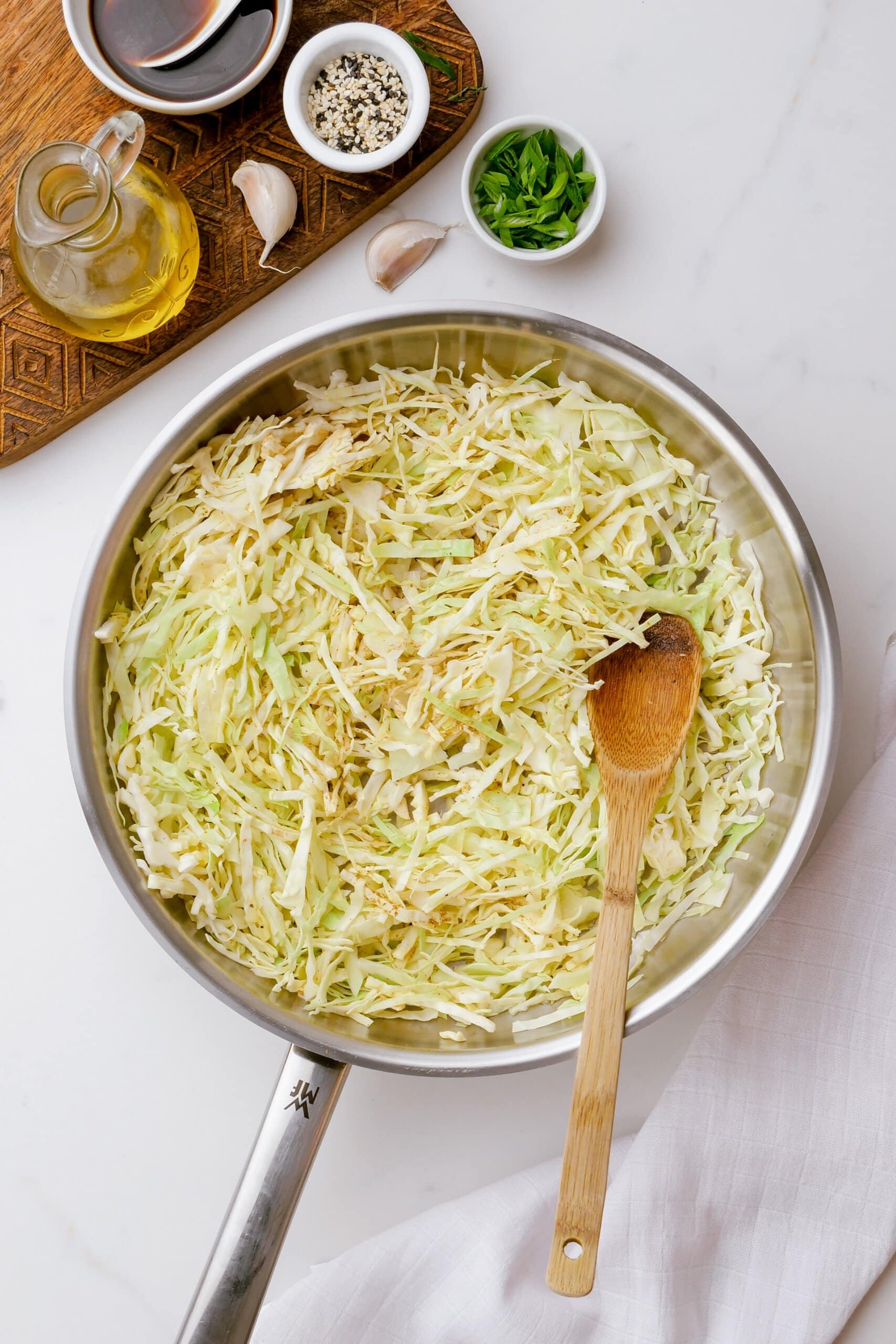 cabbage in a cooking pot with a wooden spoon