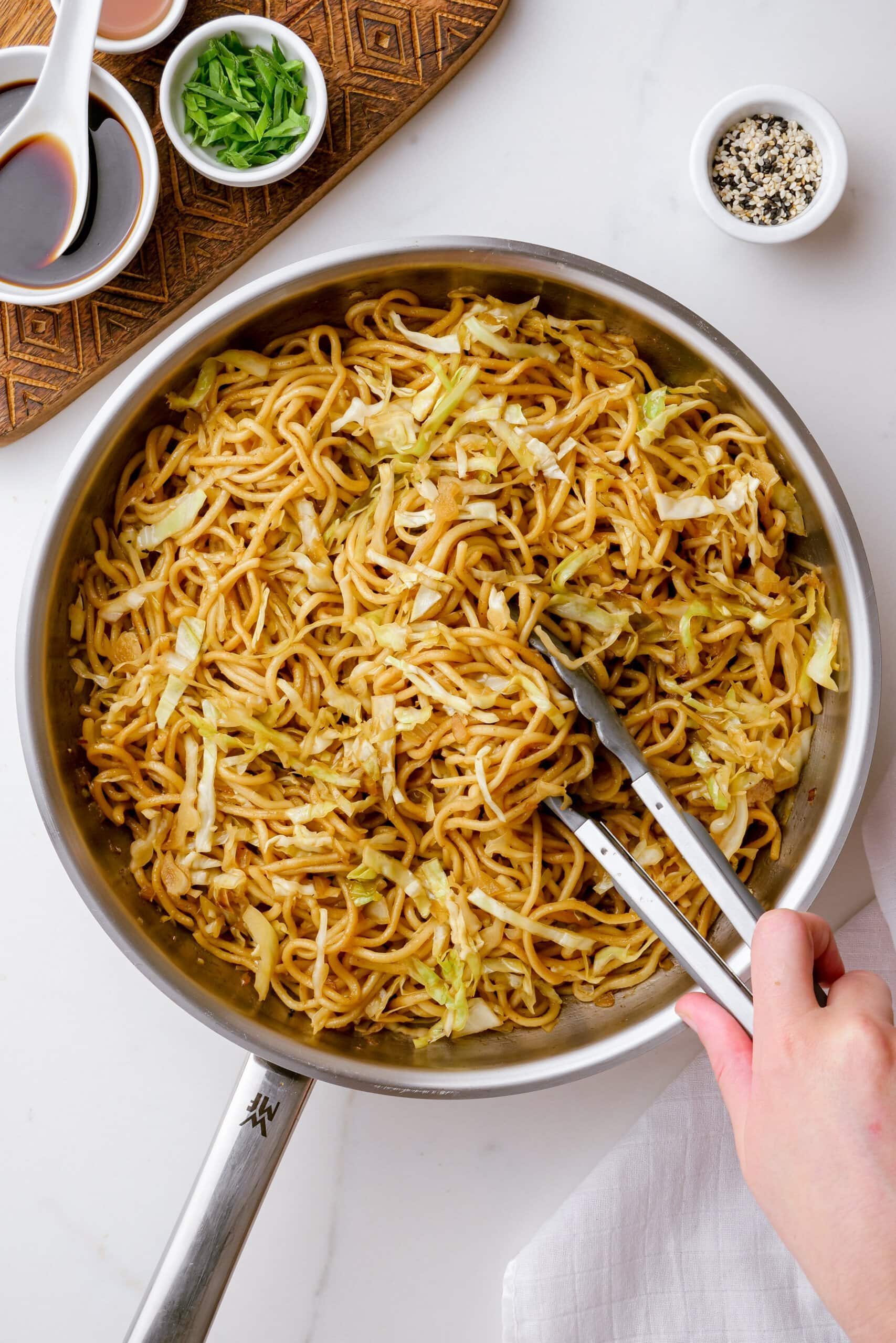 hand holding tongs into a pot of chow mein
