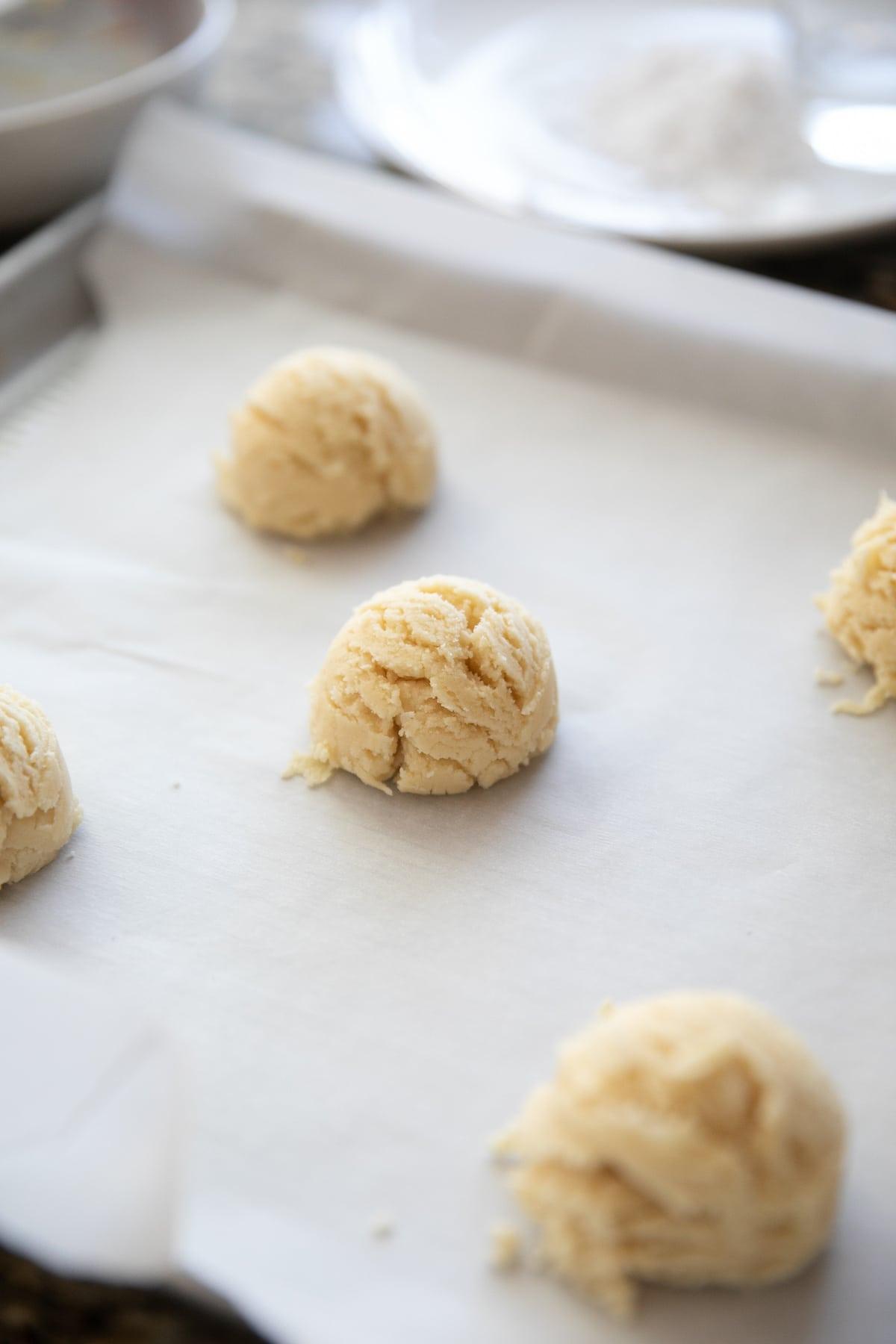 swig sugar cookie dough balls on baking sheet
