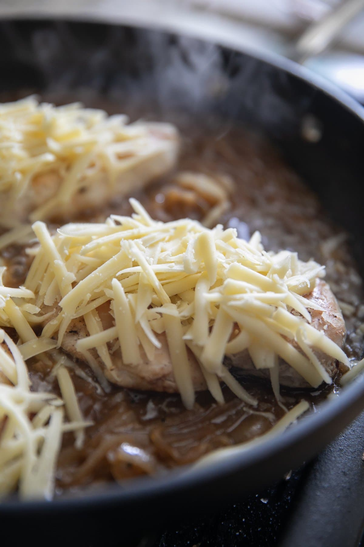 topping chicken with shredded gruyere cheese