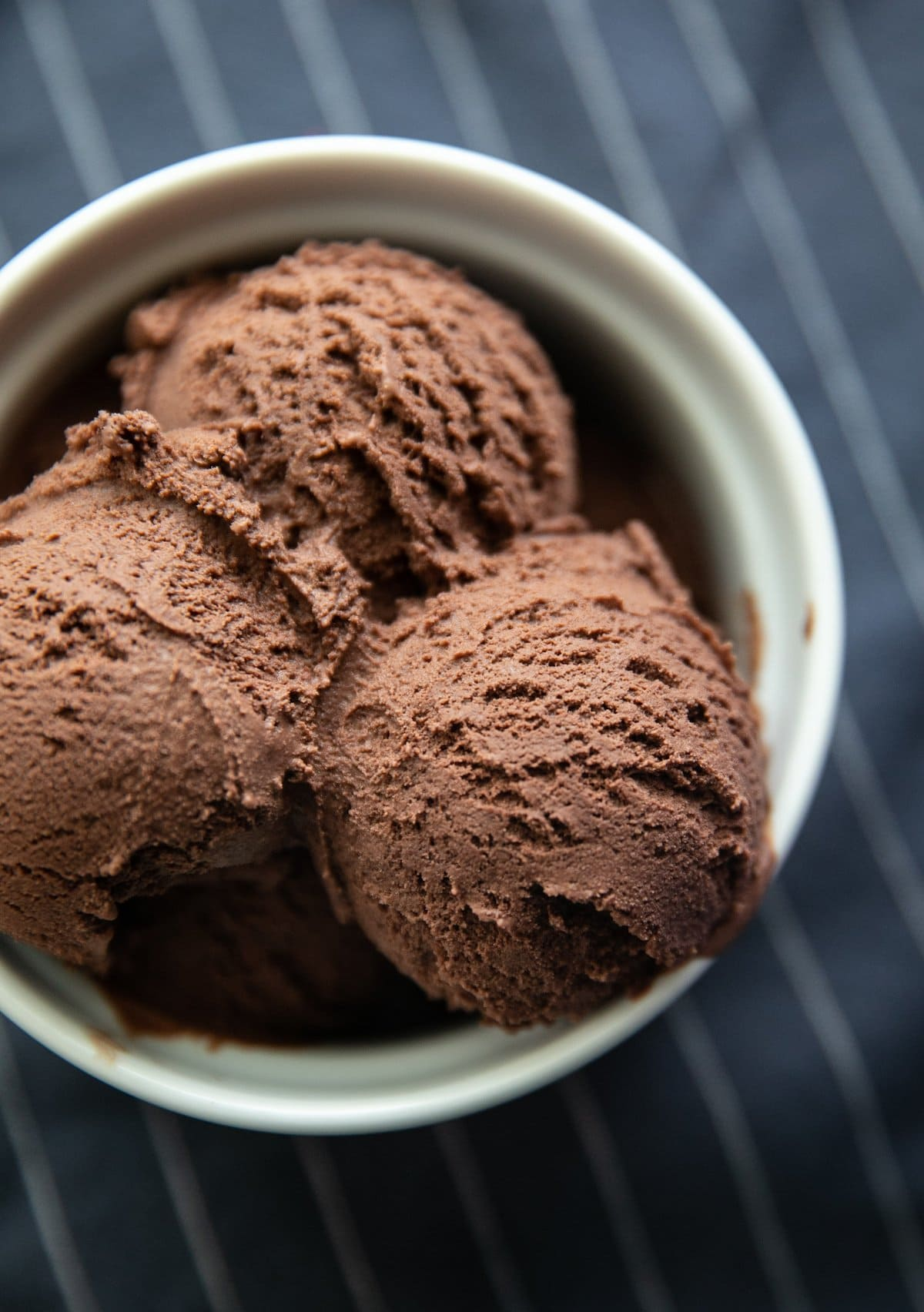 top down view of chocolate ice cream scoops in a white bowl
