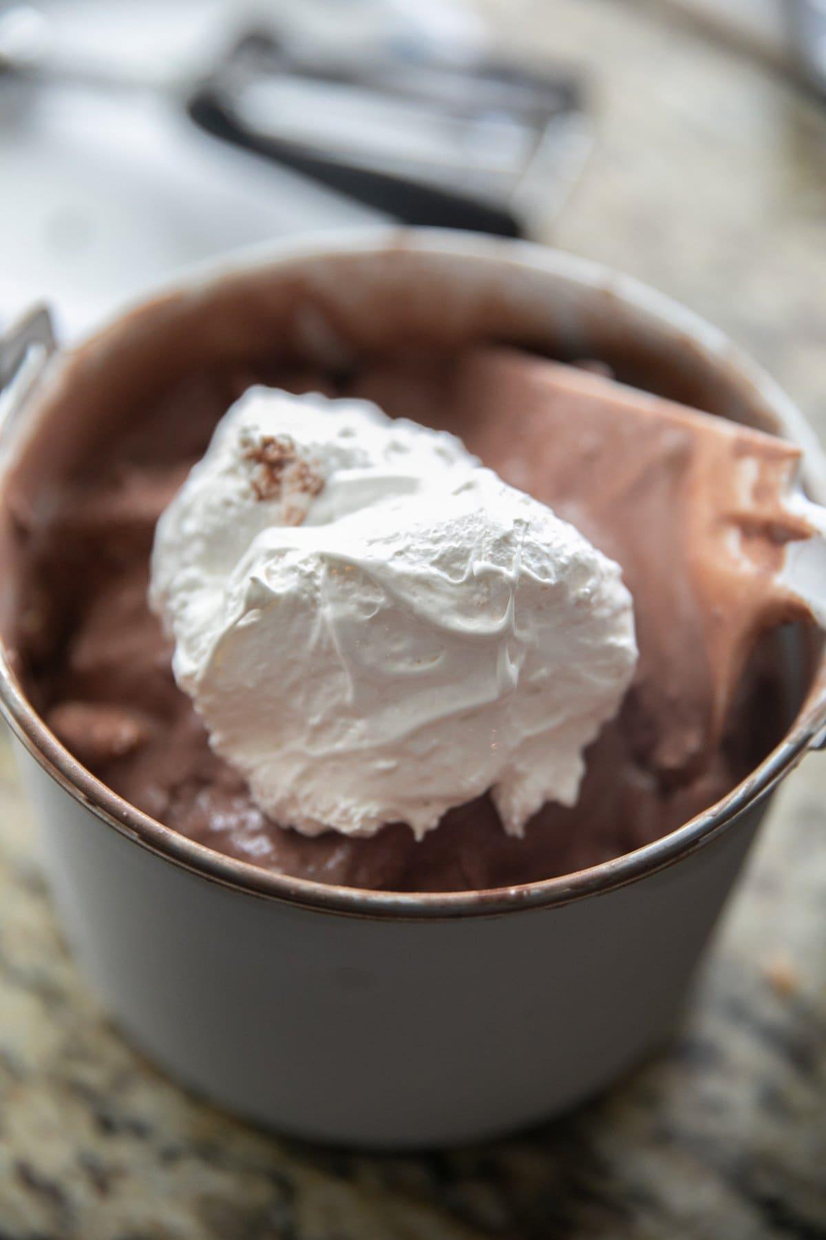 adding marshmallow fluff to freshly churned ice cream