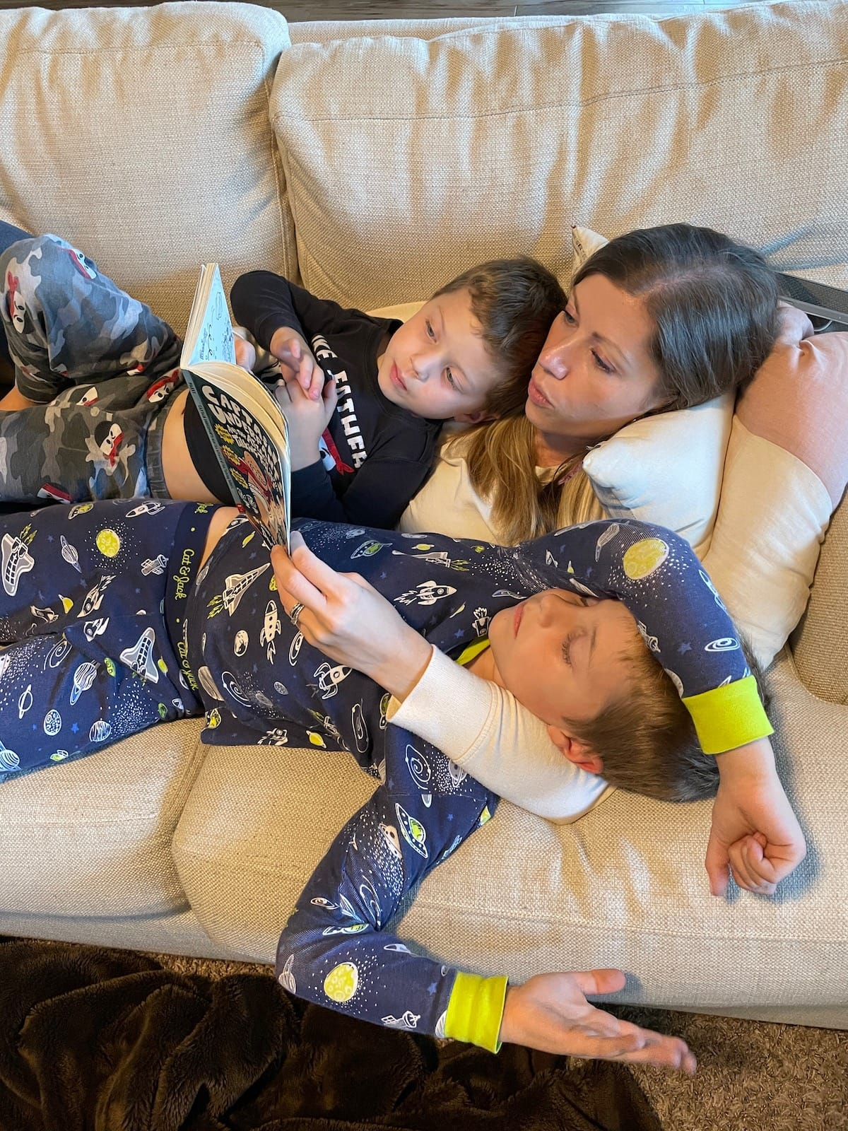 mom on couch reading to boys