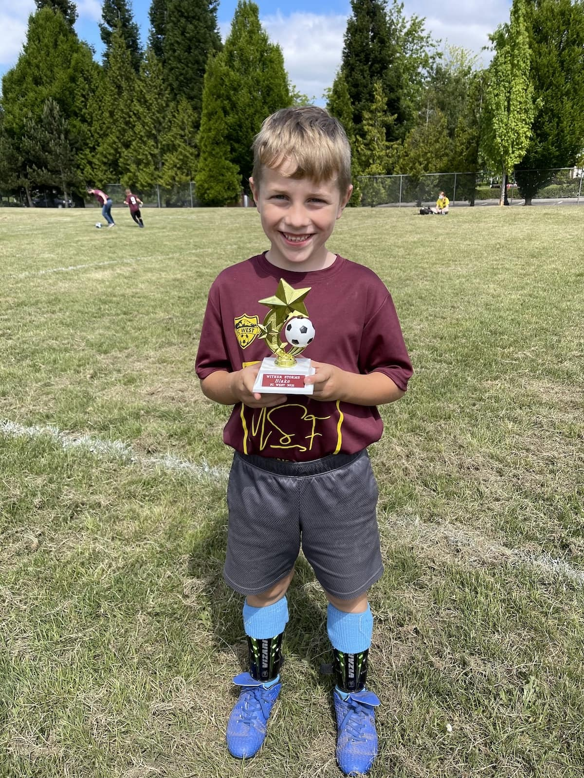 boy holding soccer trophy