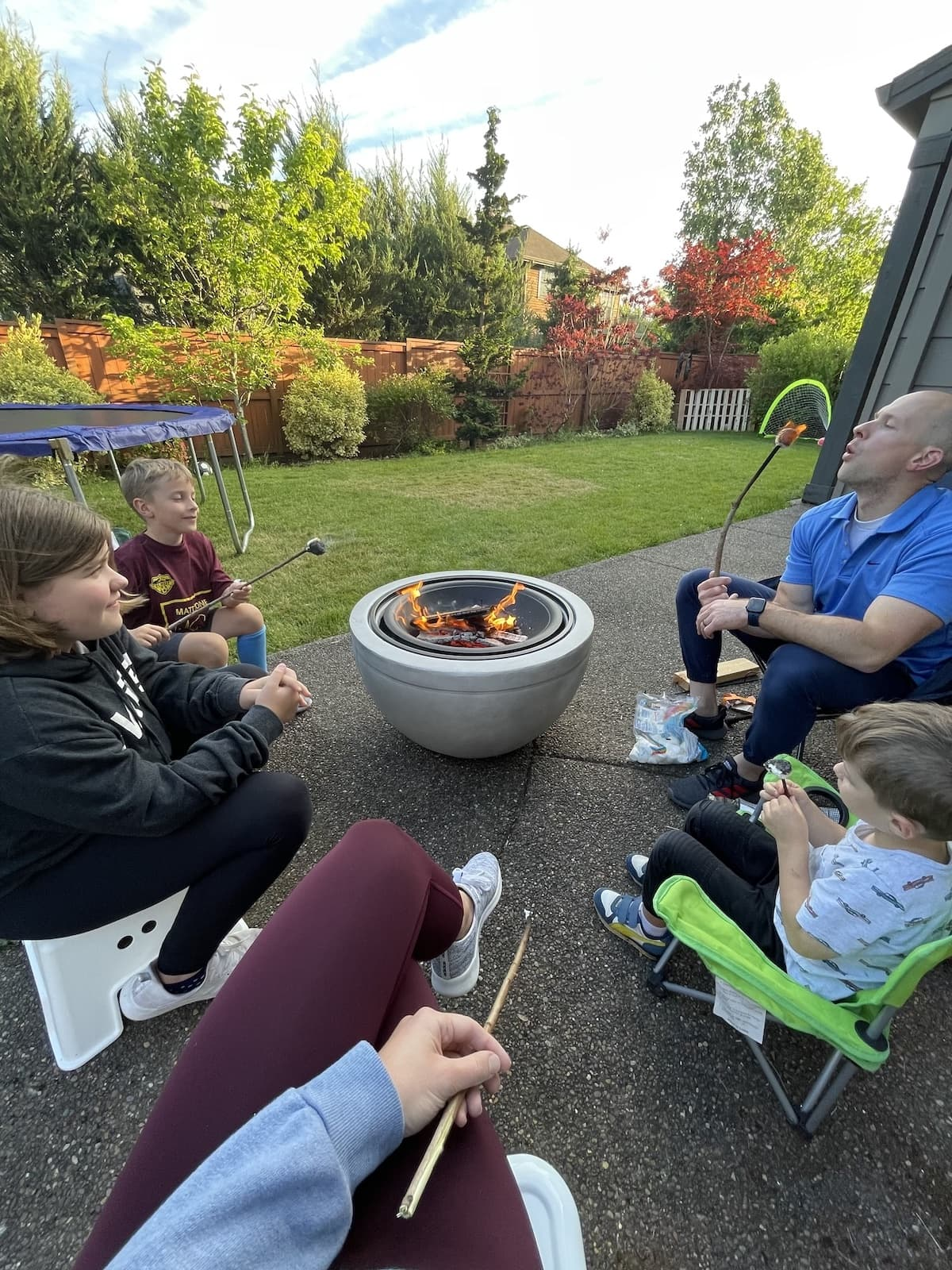 family enjoying outdoor fire pit
