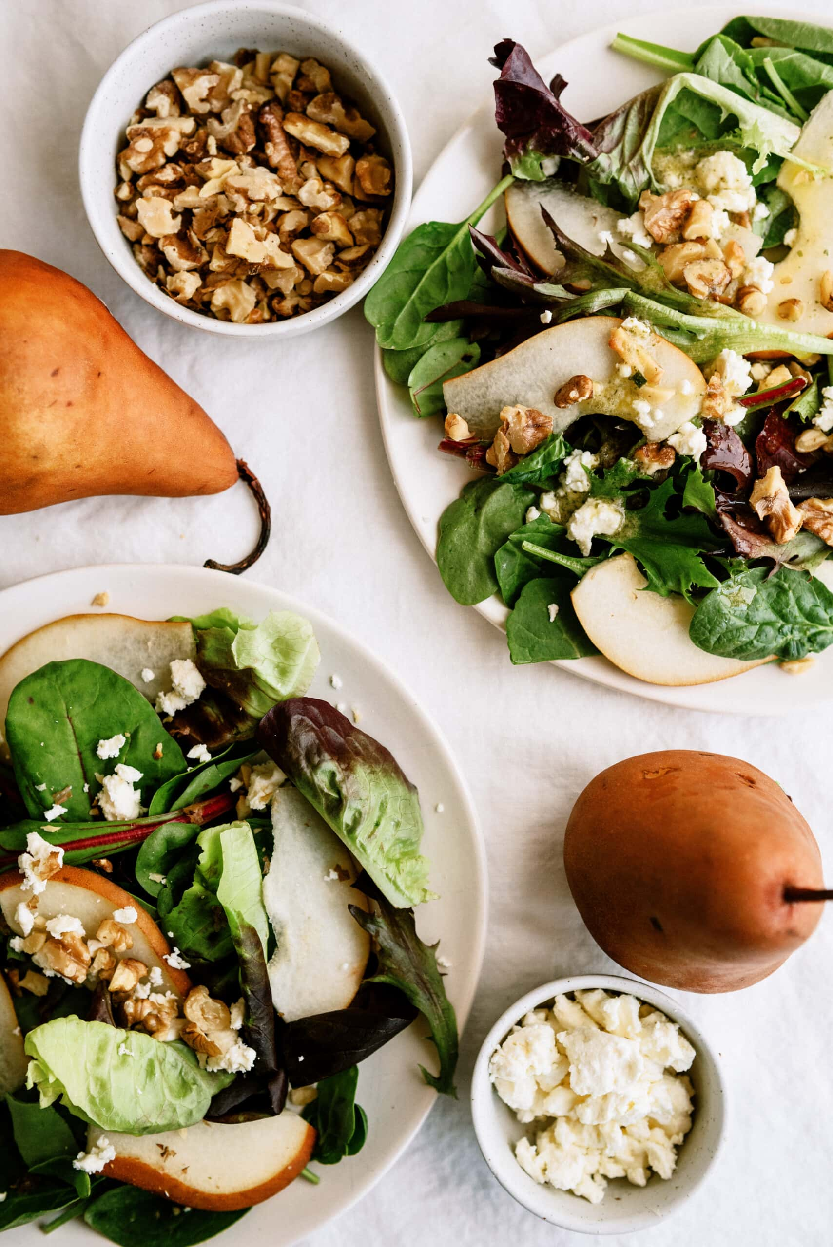 pear salads with whole pears on counter