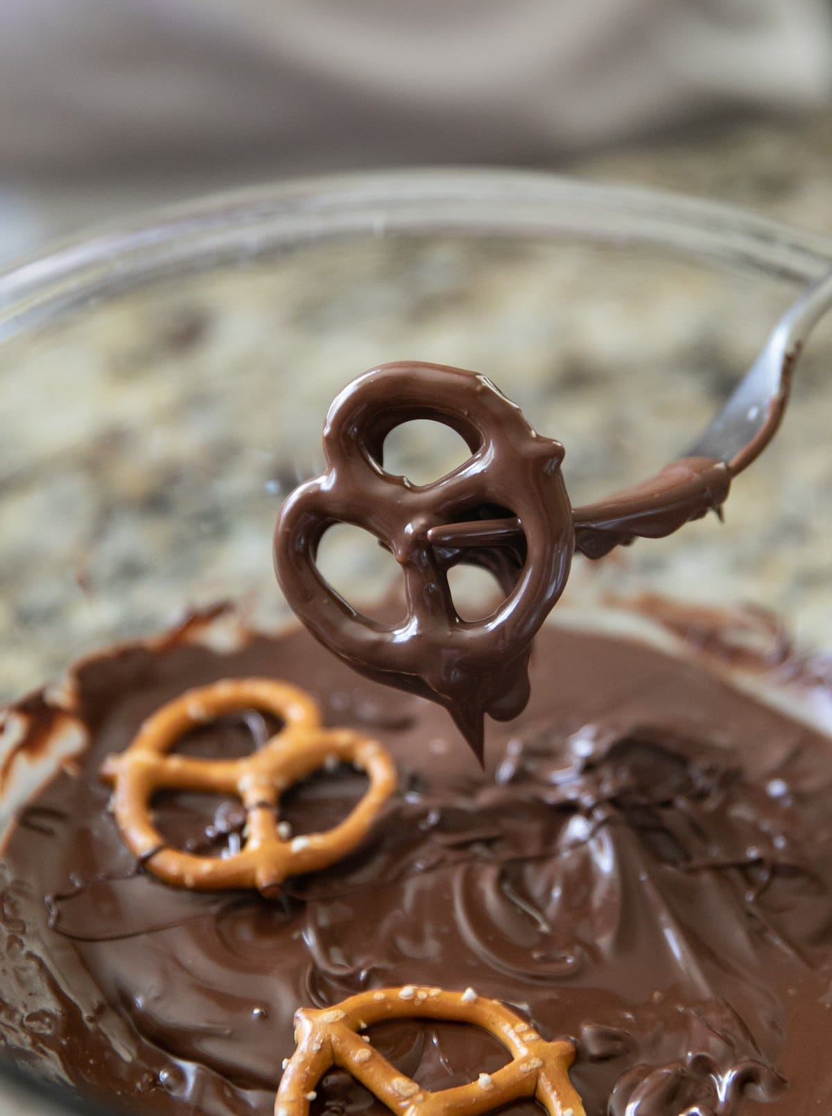 pulling chocolate covered pretzel out of melted chocolate