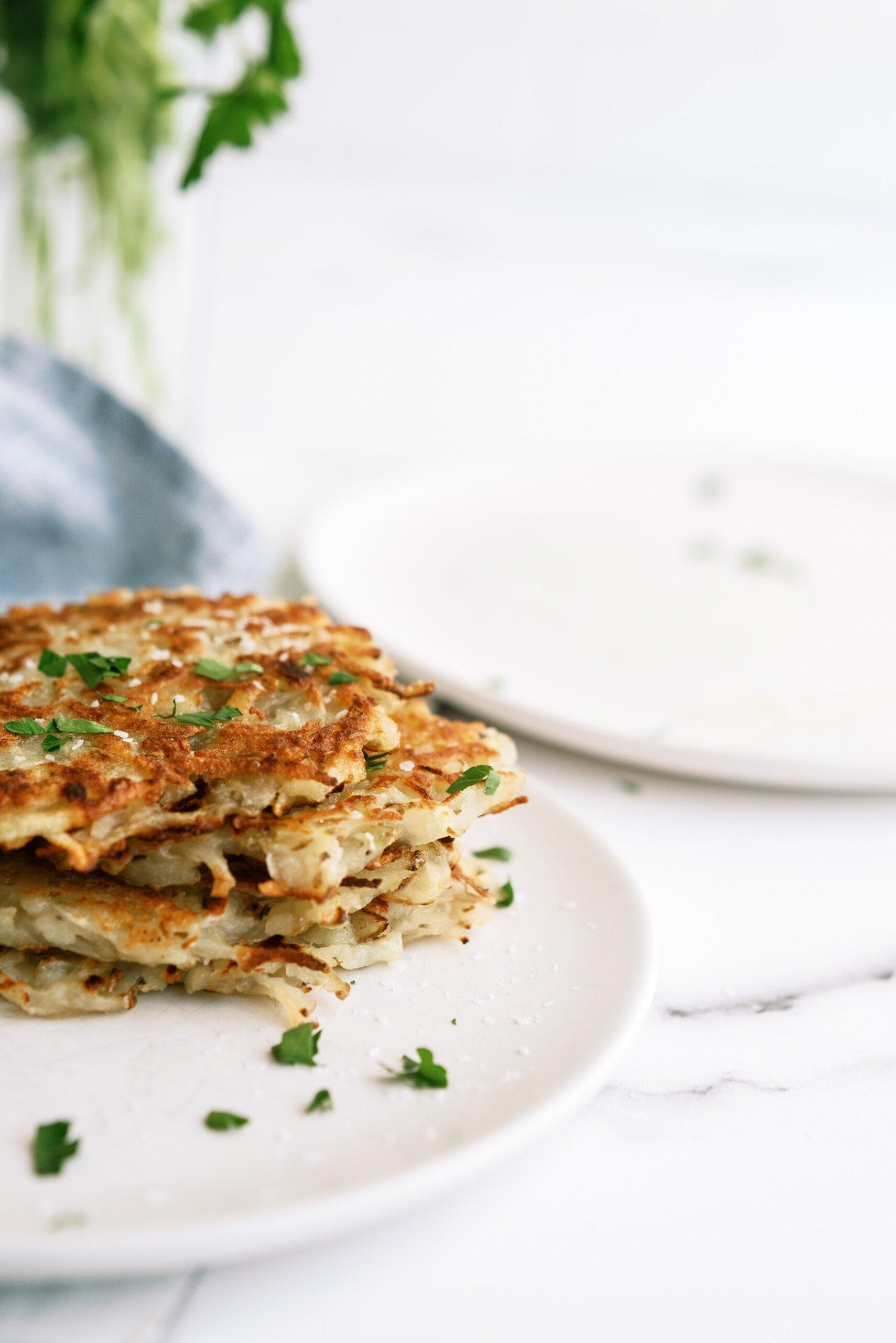 potato pancakes stacked on a white plate
