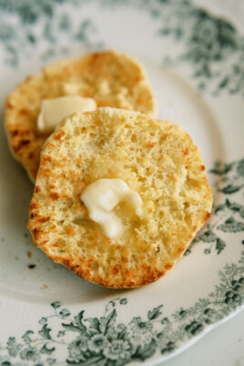 two halves of an english muffin with butter on them