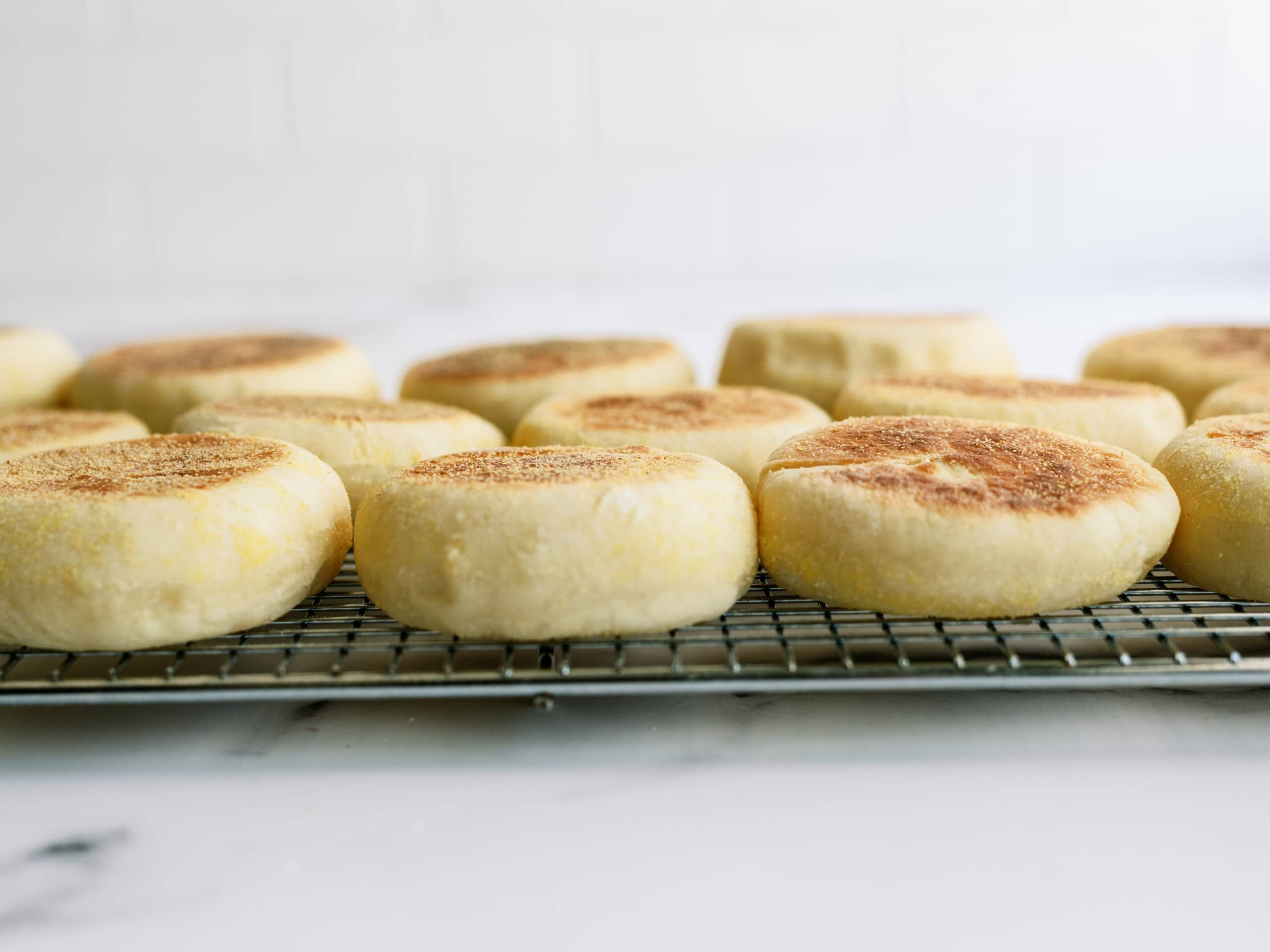 side view of english muffins on a cooling wrack