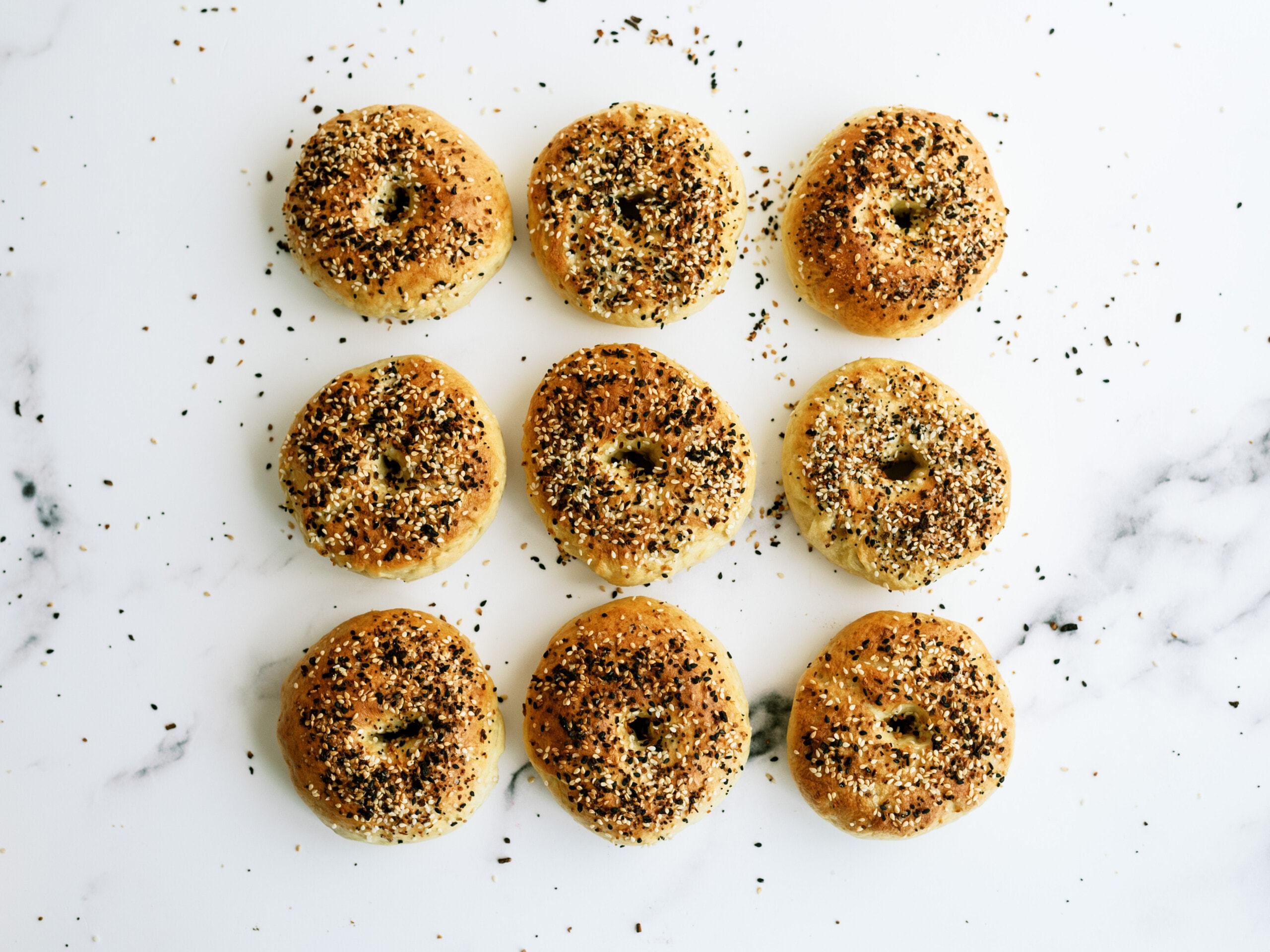 9 bagels in a 3 by 3 square on a white counter top