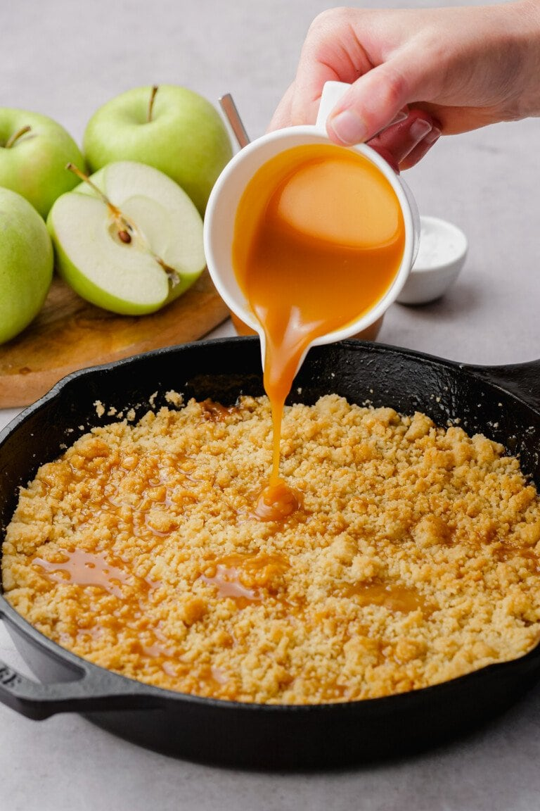 pouring more salted caramel sauce over crumble topping