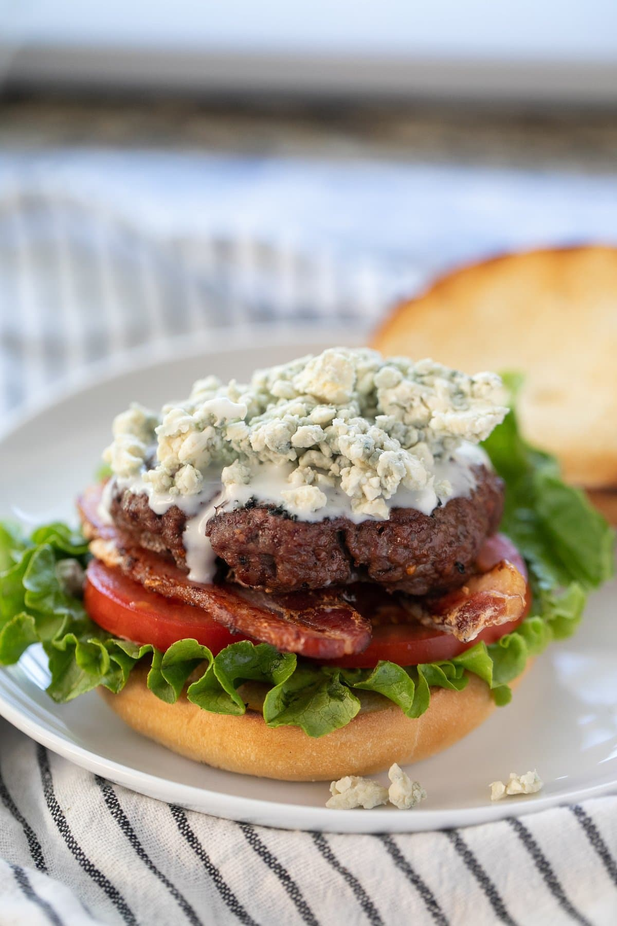 blue cheese burger with the top bun set to the side all on a white plate
