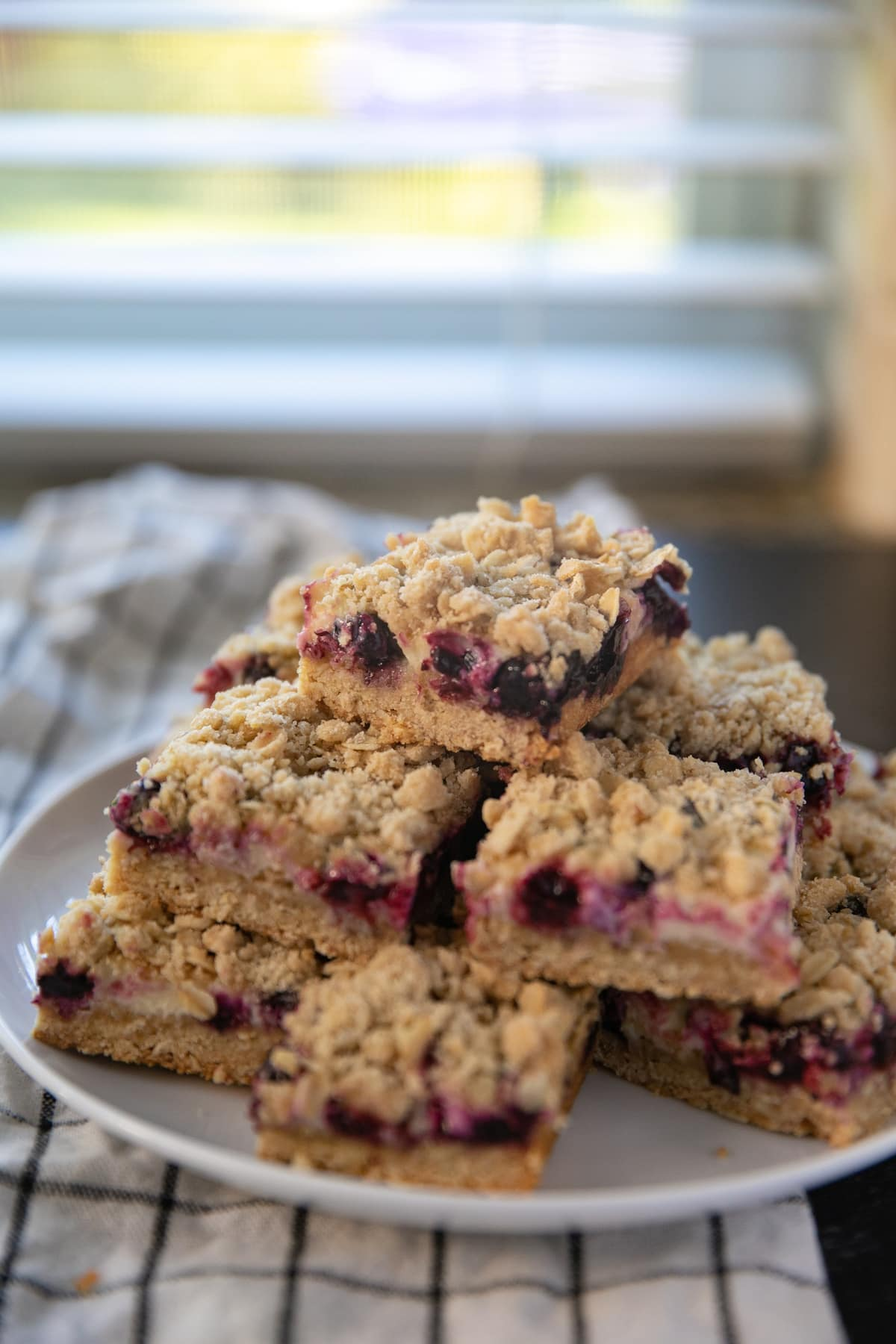 lemon blueberry bars stacked on top of each other on a white plate