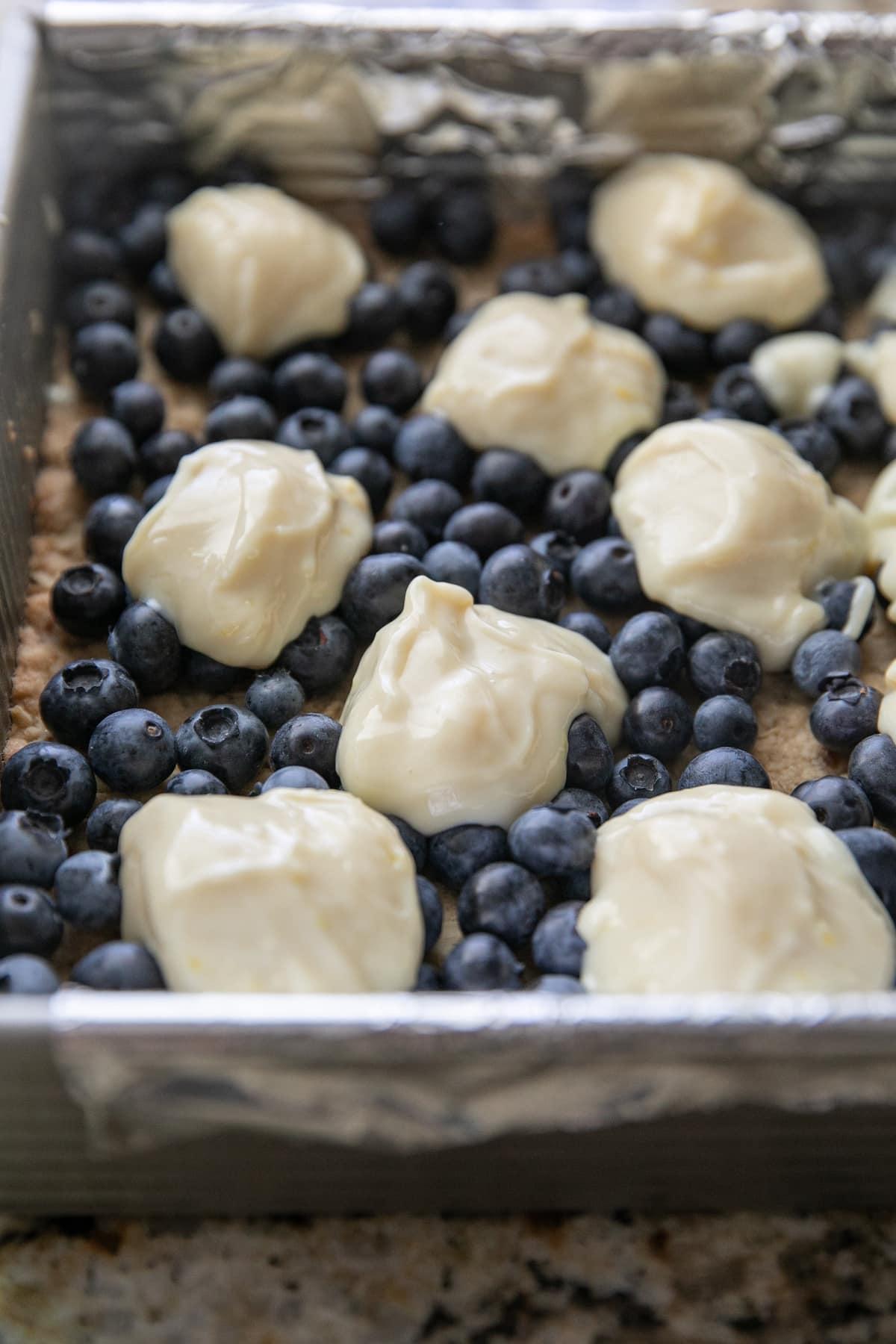 dollops of lemon mixture topping blueberries in a baking pan